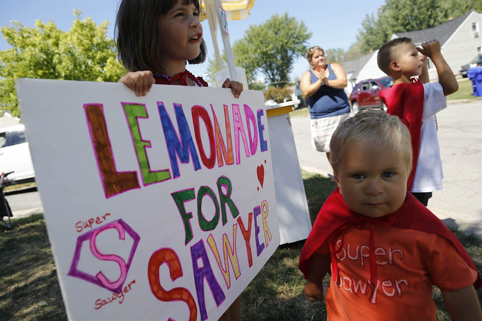From left, Disney Schunk, 6, Jace Schunk, 3, and Johnathan Dearing, 6, with help from their mom, Heather Schunk, background) run a lemonade stand to raise money for a family friend with brain cancer outside their home on Warren Avenue in West Seneca, Thursday, Aug. 4, 2016.  Sawyer Perkins, 6, a West Seneca native who now lives in Mechanicville, Va. is currently in treatment at St. Jude.  The fundraiser brought in $115 on Thursday and will run again on Sunday.  The kids will each pick out a present for Sawyer and send them along with the remainder of the money raised.
