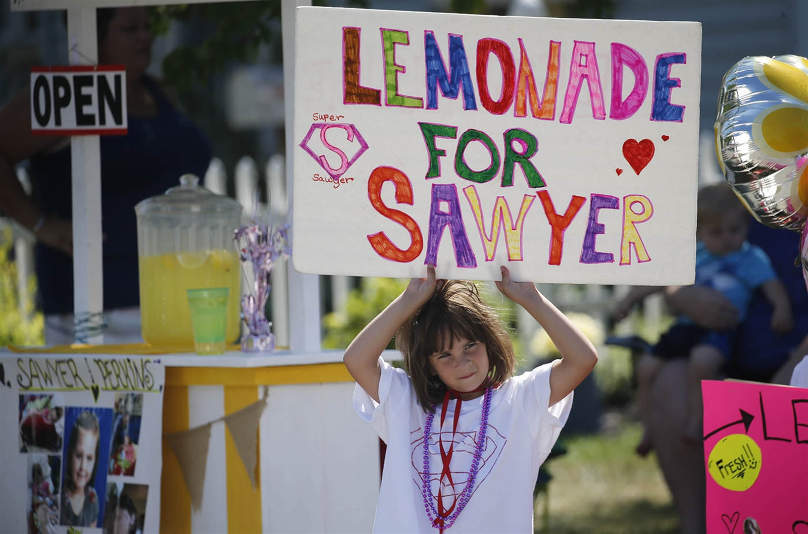 Disney Schunk, 6, holds up a sign to attract passersby to a lemonade stand her family set up to raise money for a family friend with brain cancer.