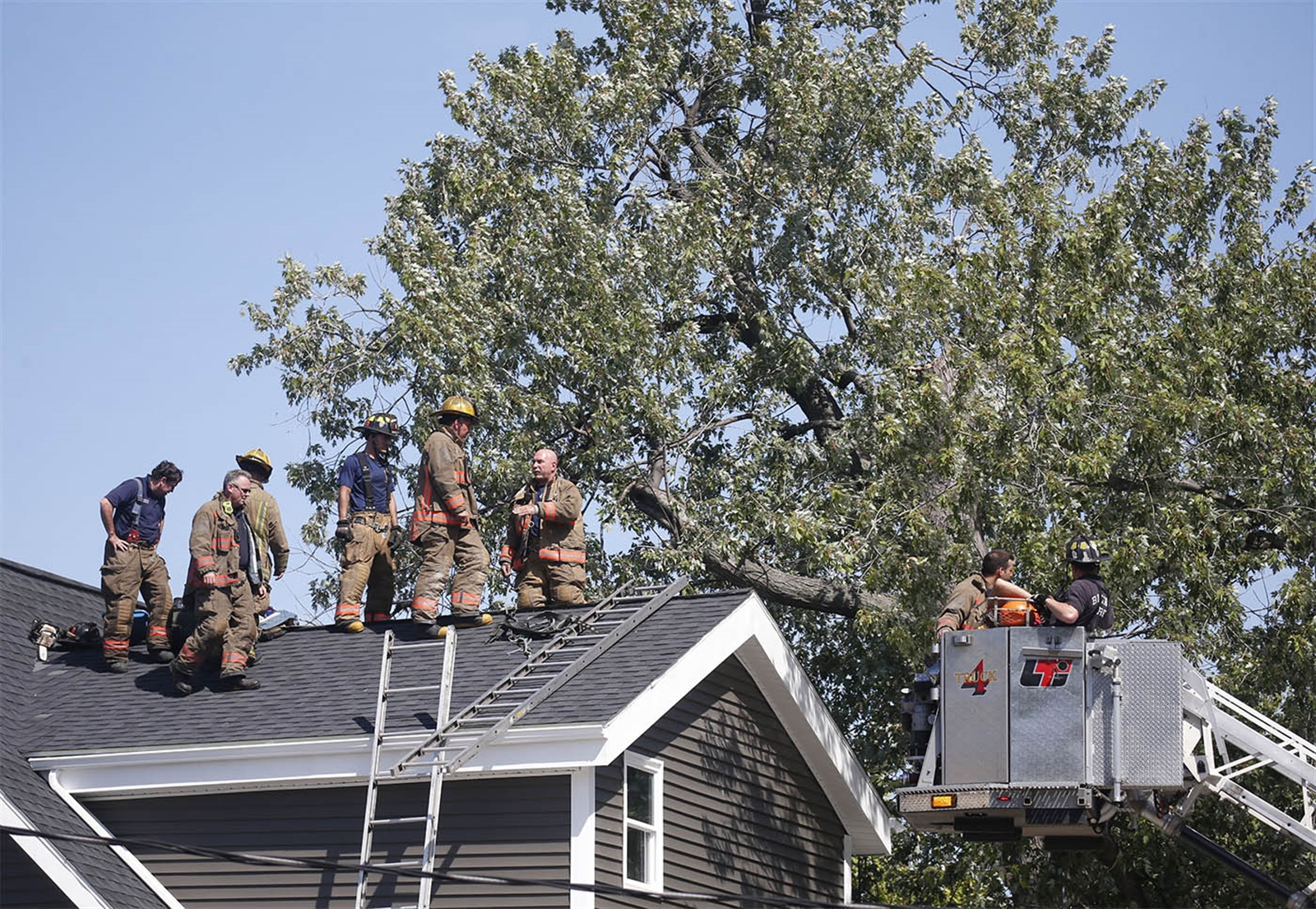 Buffalo firefighters extricate a professional tree cutter from the roof of 353 Elmwood Ave. after a large limb he was cutting fell, pinning him on the roof on Wednesday, Aug. 24, 2016.