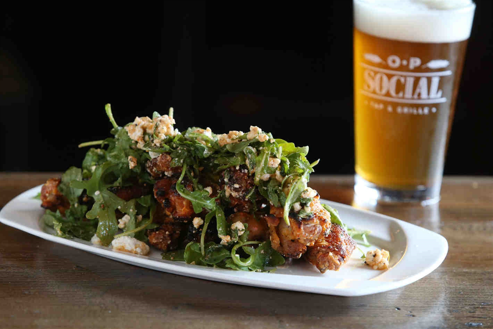 The social wings are herb marinated and artisan oven fired, tossed in spiced feta and baby arugula.