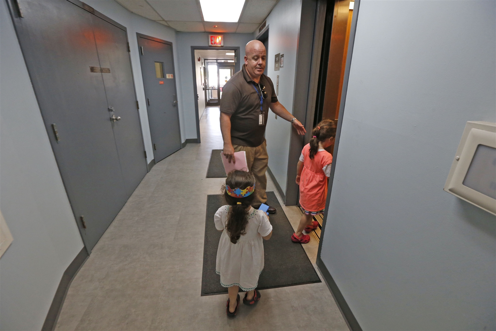 As his daughters, Marisol, 5, right entering elevator, and Mia Luz, 3, foreground, try to keep up with him in his quest, John Starkey, the new principal at Lafayette International High School, working the field, walks through the hallways of the low income Santa Maria Towers apartments hunting for students from the Hispanic community that haven't enrolled in school yet.