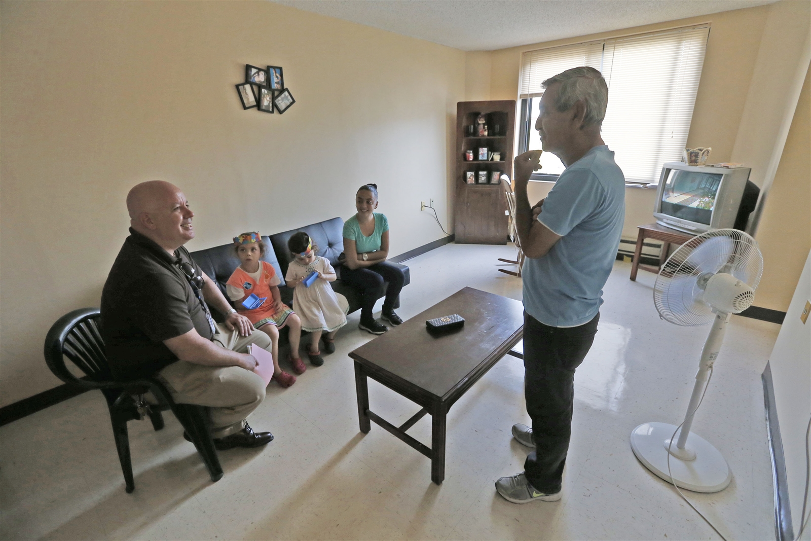 John Starkey, left, the new principal at Lafayette International High School, with his daughters Mia Luz, 3, in white, and Marisol, 5, in pink, visit the apartment of Hector Virella, standing, in the Santa Maria Towers apartments, and his daughter Angelica Viyella Torres, 19, second from right, and tries to persuade them for her to come to his school.