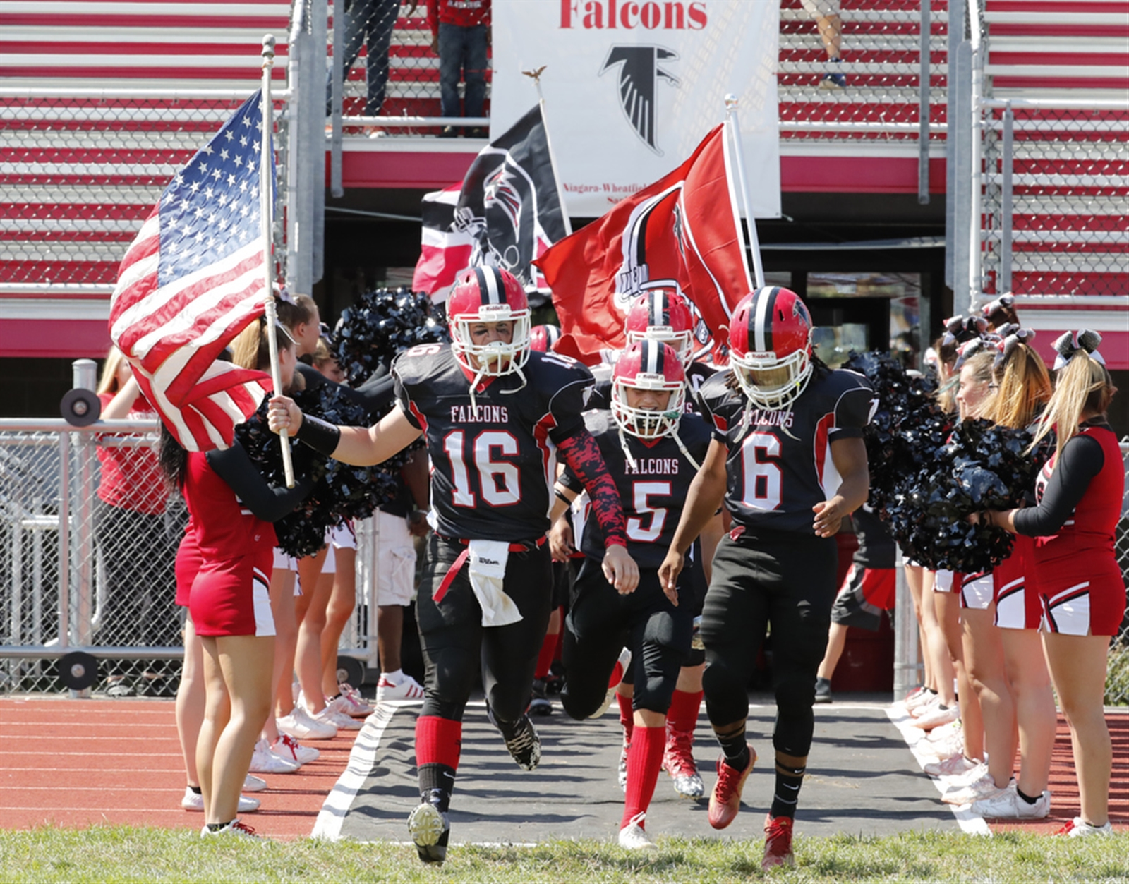 Niagara Wheatfield's Phil Mona carries the American flag during introductions prior to playing Grand Island at Niagara Wheatfield High school on Saturday, Sept. 3, 2016.