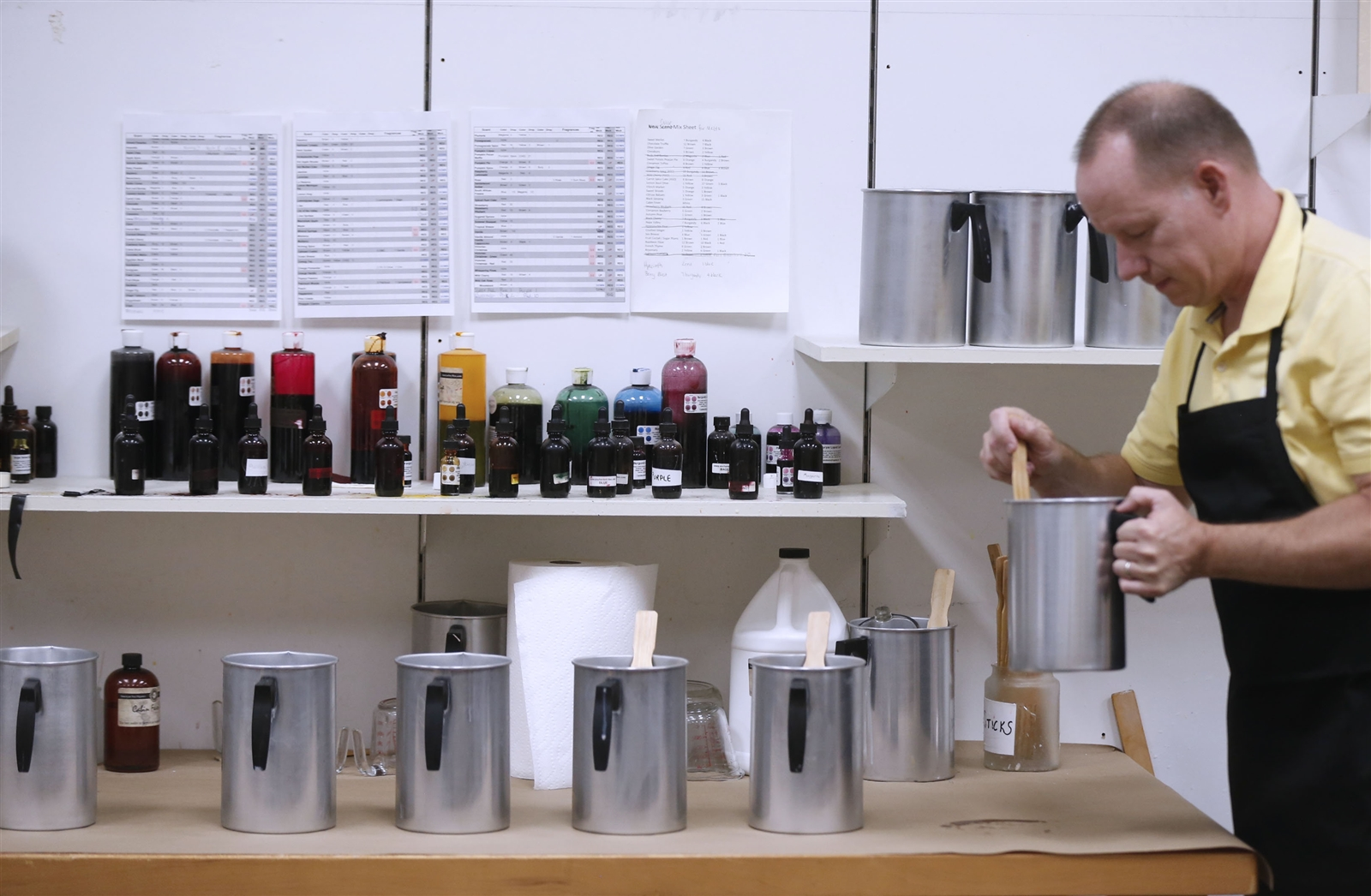 Jeff Schumacher mixes soy wax before pouring out scented candles.