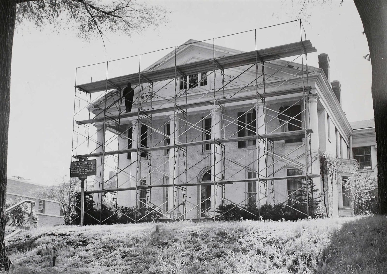 "A 1965 Buffalo Evening News photograph by photographer Robert M. Metz shows scaffolding outside the Wilcox Mansion as restoration began. First built to be a military officer's quarters in 1838 it was known as the ""Buffalo Barracks"". Dexter Rumsey purchased the house in 1883 as a wedding gift for his daughter, Mary Grace, who married a young Buffalo lawyer, Ansley Wilcox. The Wilcox family made 641 Delaware Avenue their home from 1883 to 1933."