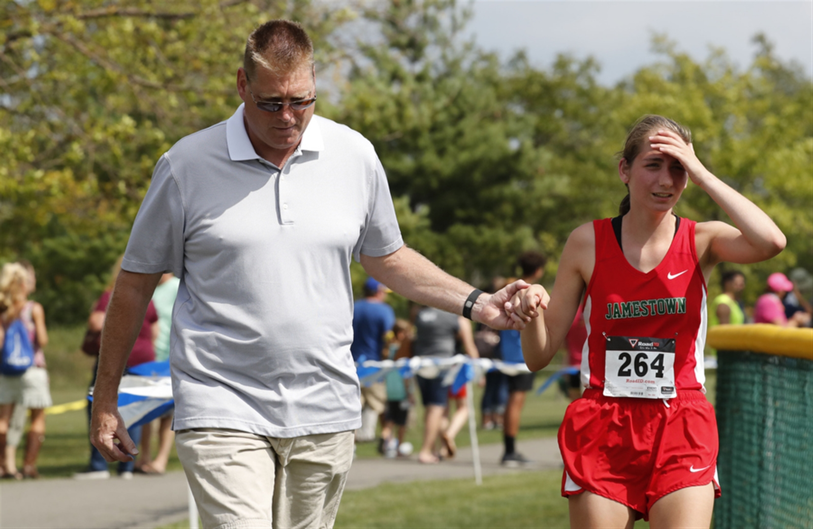 Walter Hoss holds his daughter Nicole's hand as they walk to the the finish line as she overheated as she competed in the large schools girls cross country meet  at Sunshine Park in West Seneca on Saturday, Sept. 10, 2016.