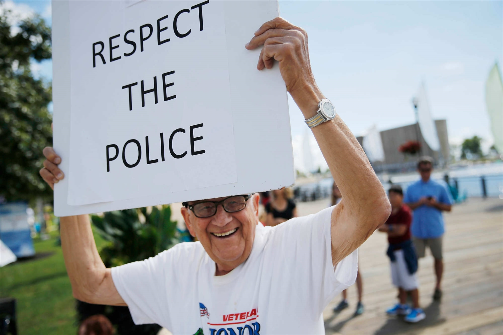 "Edward Posluszny, 91, of Buffalo, a World War II veteran, holds up a sign reading ""Respect the police"" during the Peace-Justice-Nonviolence Festival and Walk of Peace at Canalside, Sunday, Sept. 11, 2016."