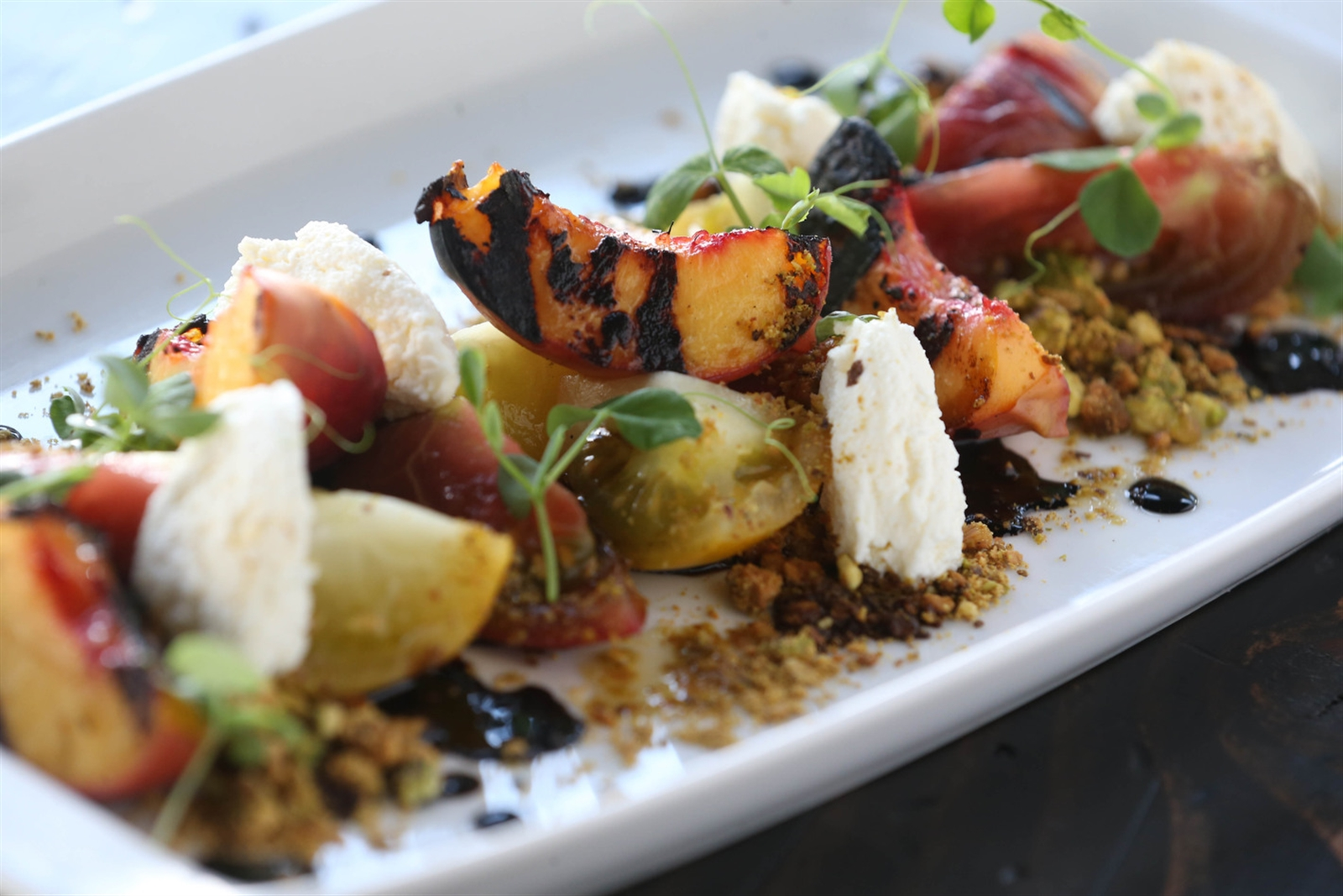 The grilled peach and tomato salad is made with local peaches, Wierzbic Farm heirloom tomatoes, housemade ricotta and pistachio balsamic.