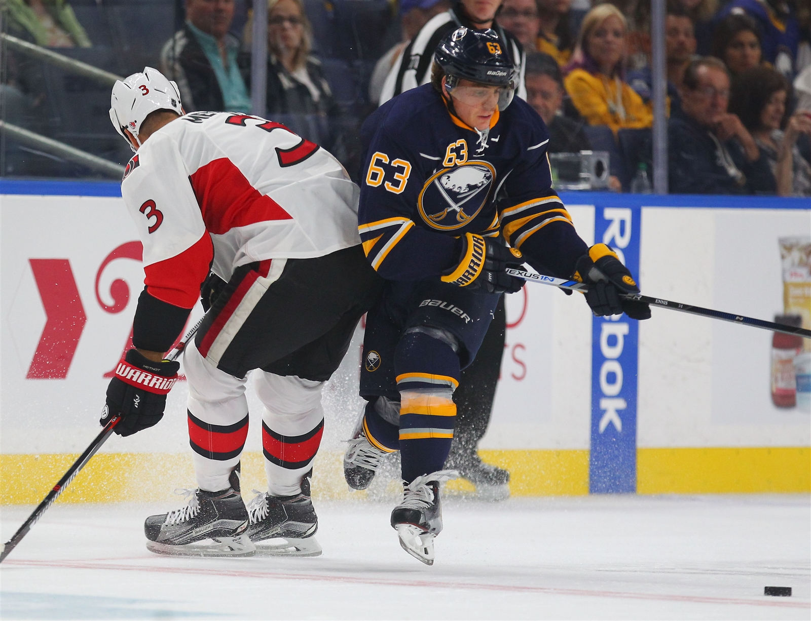 Tyler Ennis tries to avoid the check of the Senators' Marc Methot.