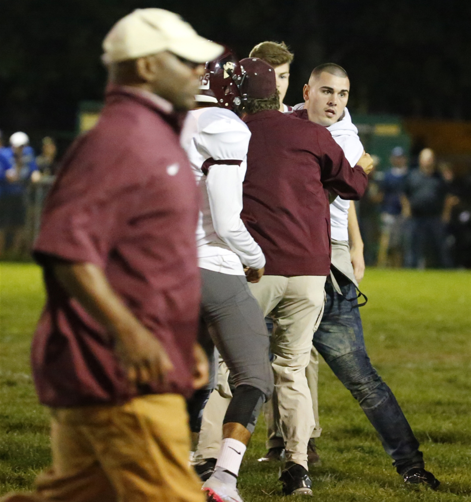 St. Joe's alumni Chad Kelly is restrained after leaving the stands to come to the aid of his brother Casey.