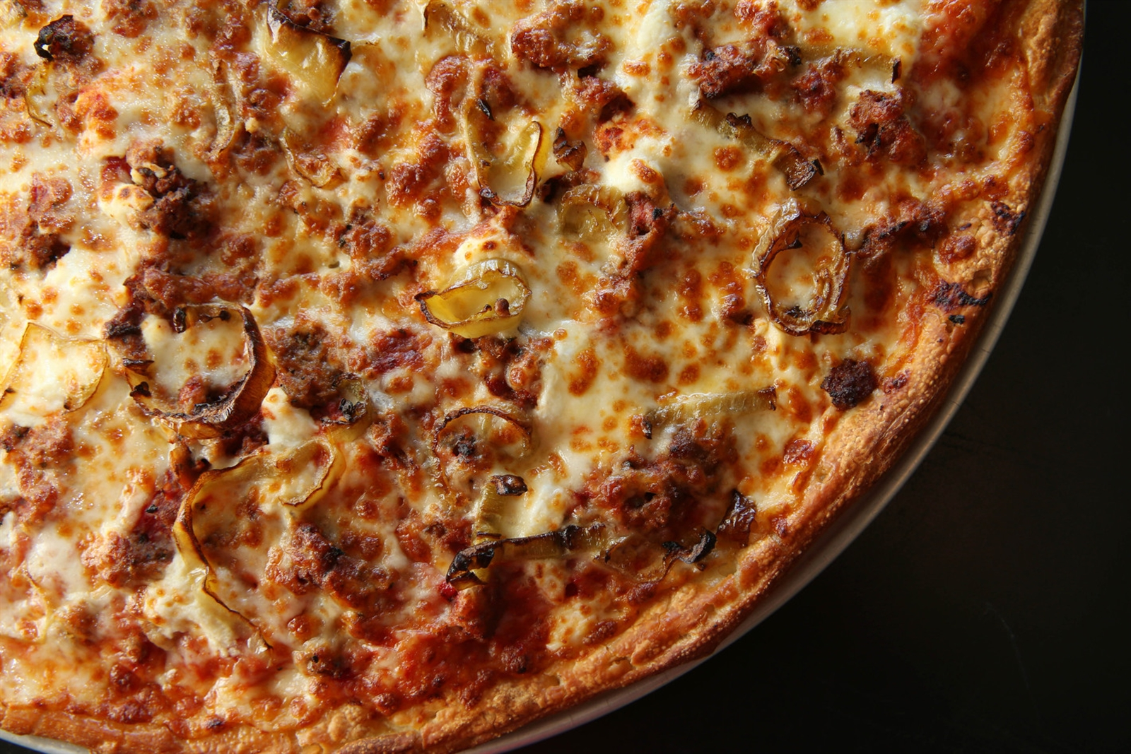 The cheesesteak pizza is  a white pizza topped with steak, mozzarella, fontina cheddar/jack, Romano, hot banana peppers, dried onions and a special sauce.