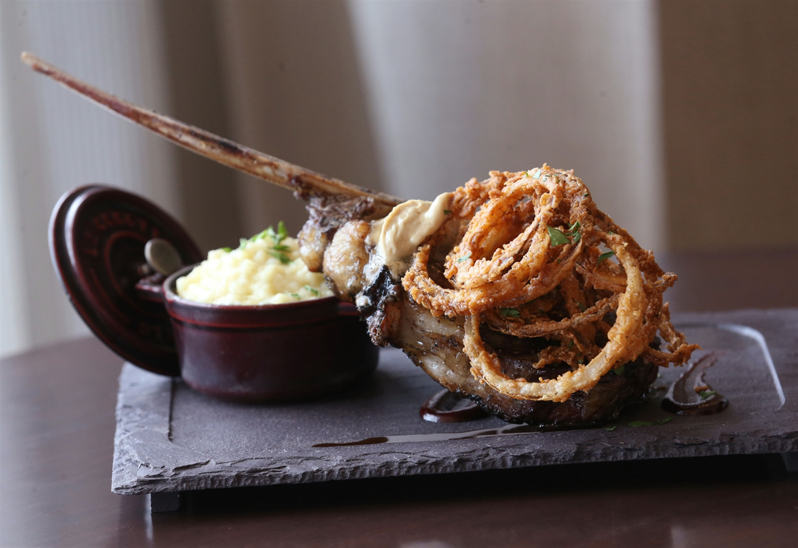 The tomahawk steak is a 22-ounce center cut with truffled whipped potato, buttermilk onion straws, a Bordeaux and cherry reduction and foie butter.