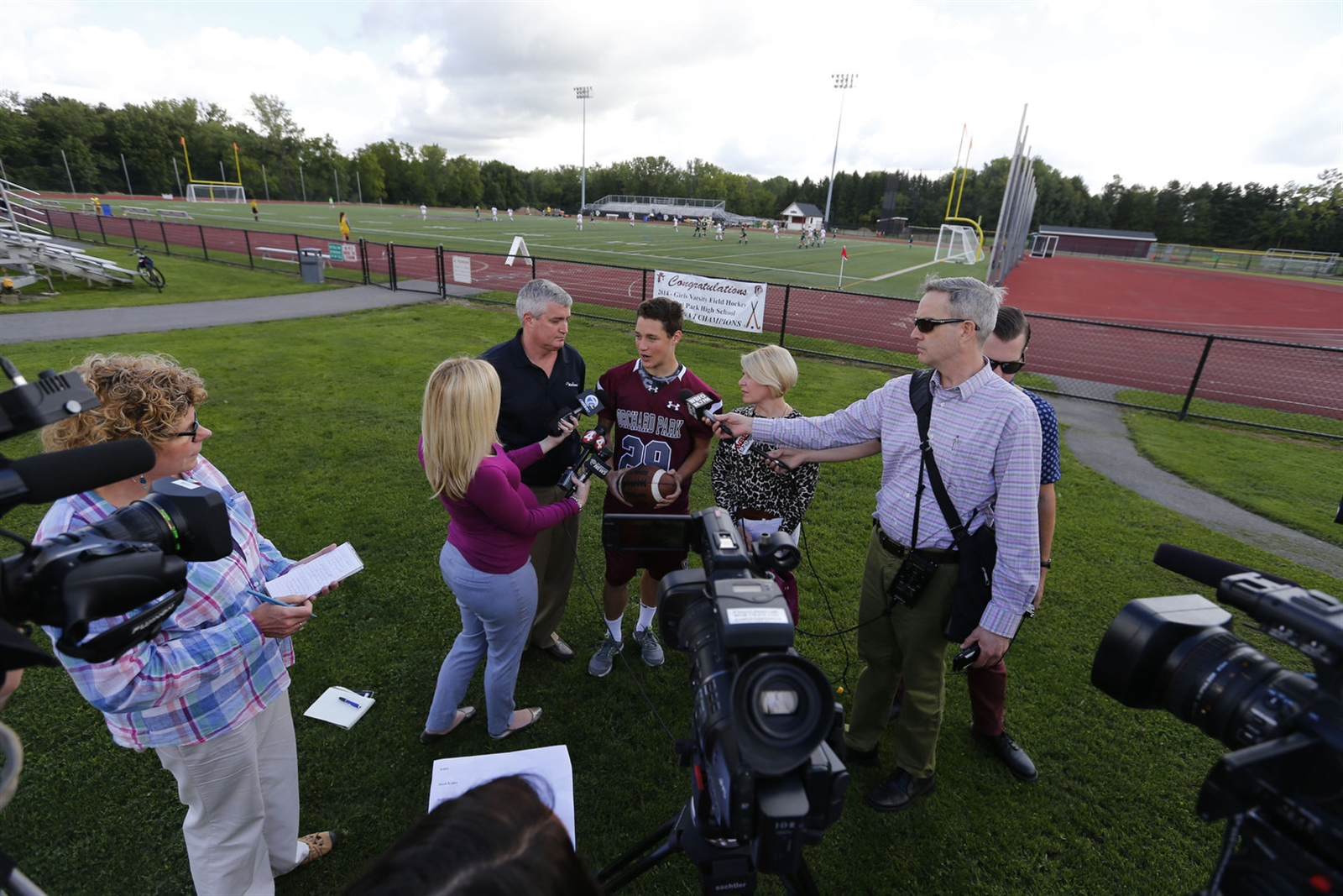 Jacob Kohler and his parents, Scott and Lisa, speak with the media Sept. 2 at Orchard Park High School after New York State Education Commissioner MaryEllen Elia granted a stay, allowing him to play that night and through the season.