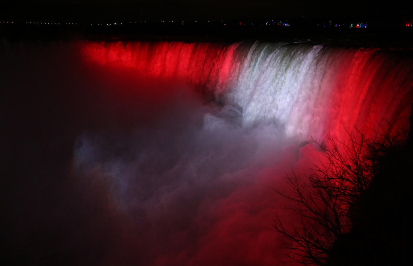 The Horseshoe Falls is lit up in vibrant red and white.