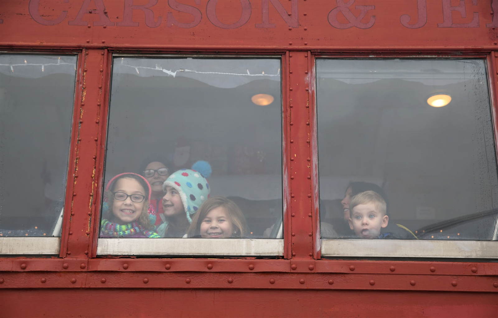 Children from the Ruh, Gleason, Horton and Pietrcak families look out the window shortly before the ride begins.