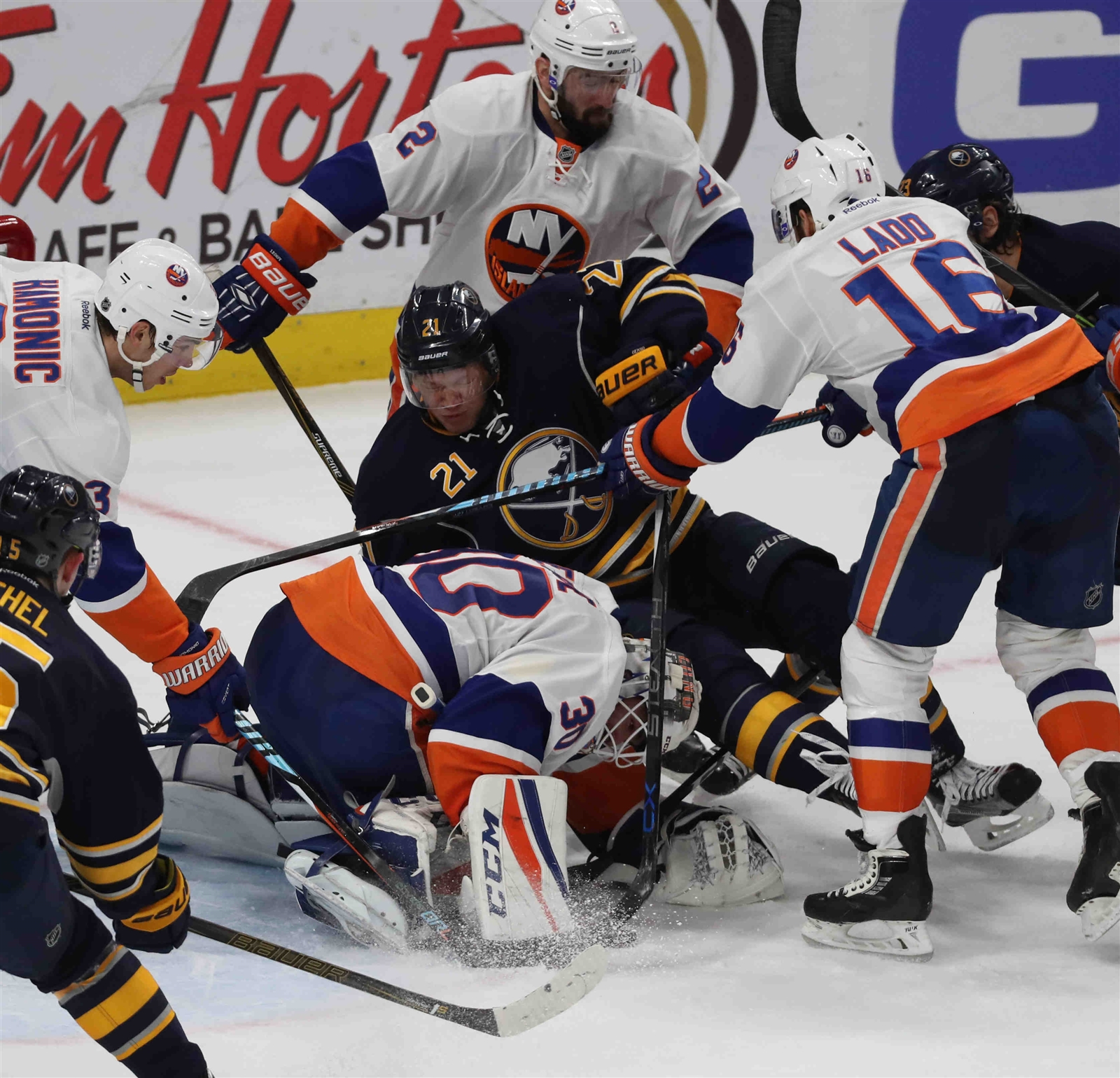 Buffalo Sabres right wing Kyle Okposo (21) battles New York Islanders goalie Jean-Francois Berube (30) for the puck.