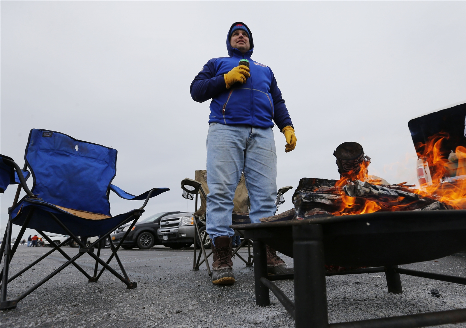 Bills fan Wesley McDonald stays warm by the fire before the game.