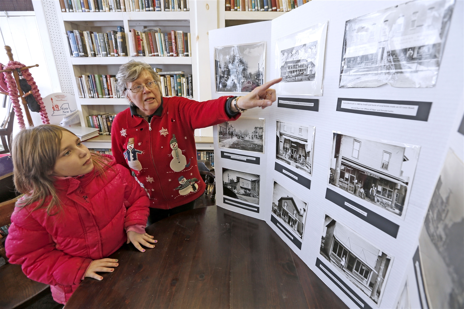 Town historian and librarian Sharon Howe  discusses vintage photos of the Village of Cherry Creek with Shawna Nichols, 9, a Pine Valley Central School second-grader, at the Cherry Creek Library on Feb. 3.