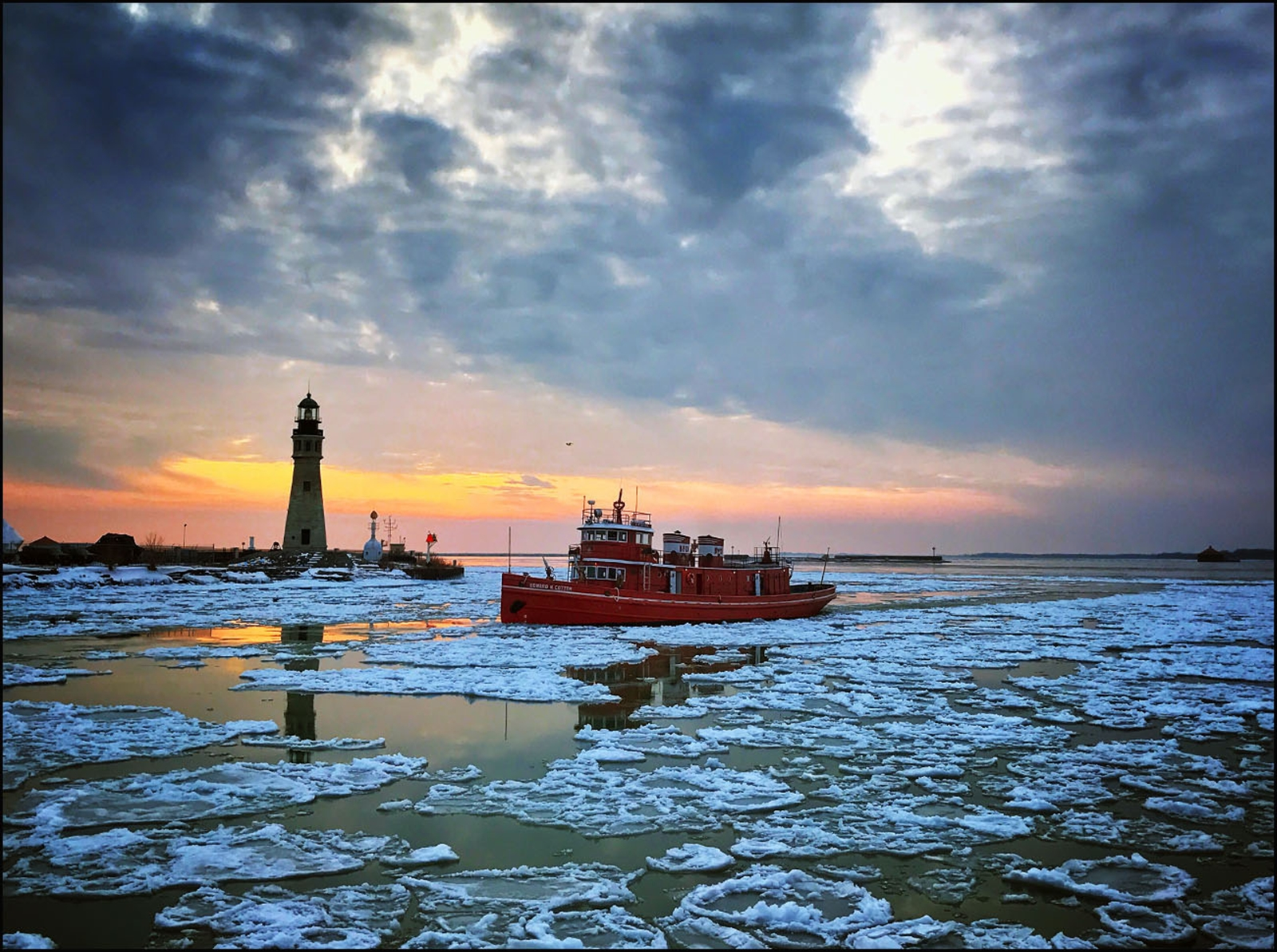 The Buffalo fireboat Edward M. Cotter moves past the lighthouse at sunset as it breaks the ice in the Buffalo River.