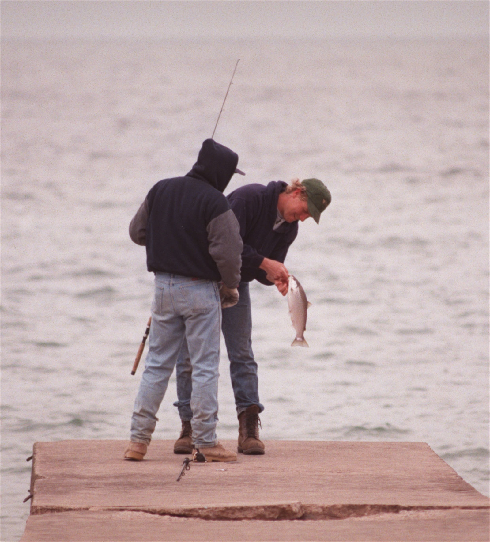 From April 1999:  Francis Holly, right, gets a catch as he and Kurt Hayes did some fishing after work on a turbulent Lake Ontario at Krull Park in Olcott.  He caught a rainbow trout.