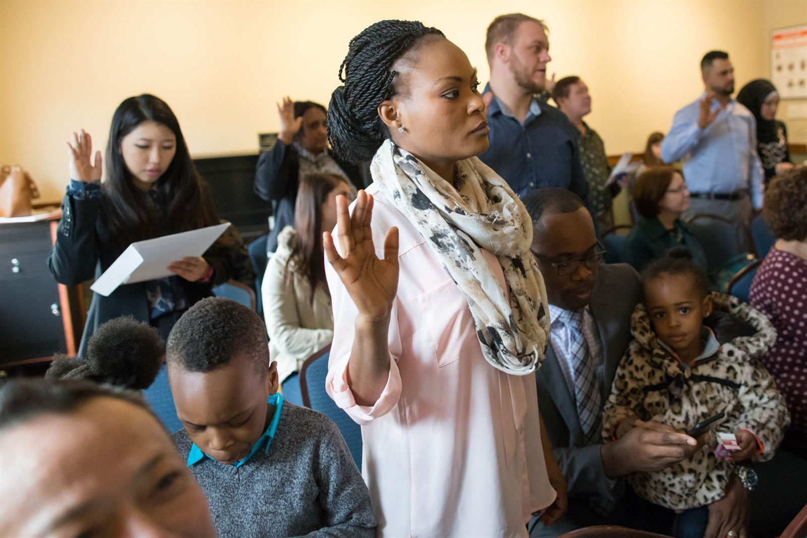 Patricia Suteh of Nigeria is surrounded by her family, husband K.C., son Kemene, 5, and daughters Kezor, 3, and Lenu, 2, as she takes the oath of allegiance to become a United States citizen.