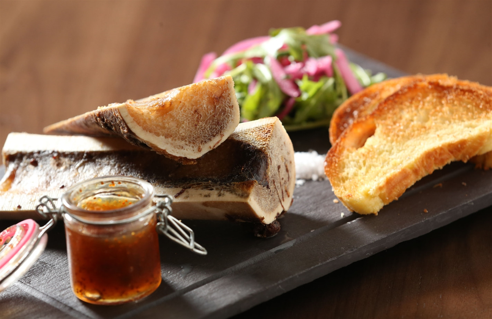 Their roasted bone marrow comes with pickled shallot, baby arugula salad, fig preserve and truffle crostini.