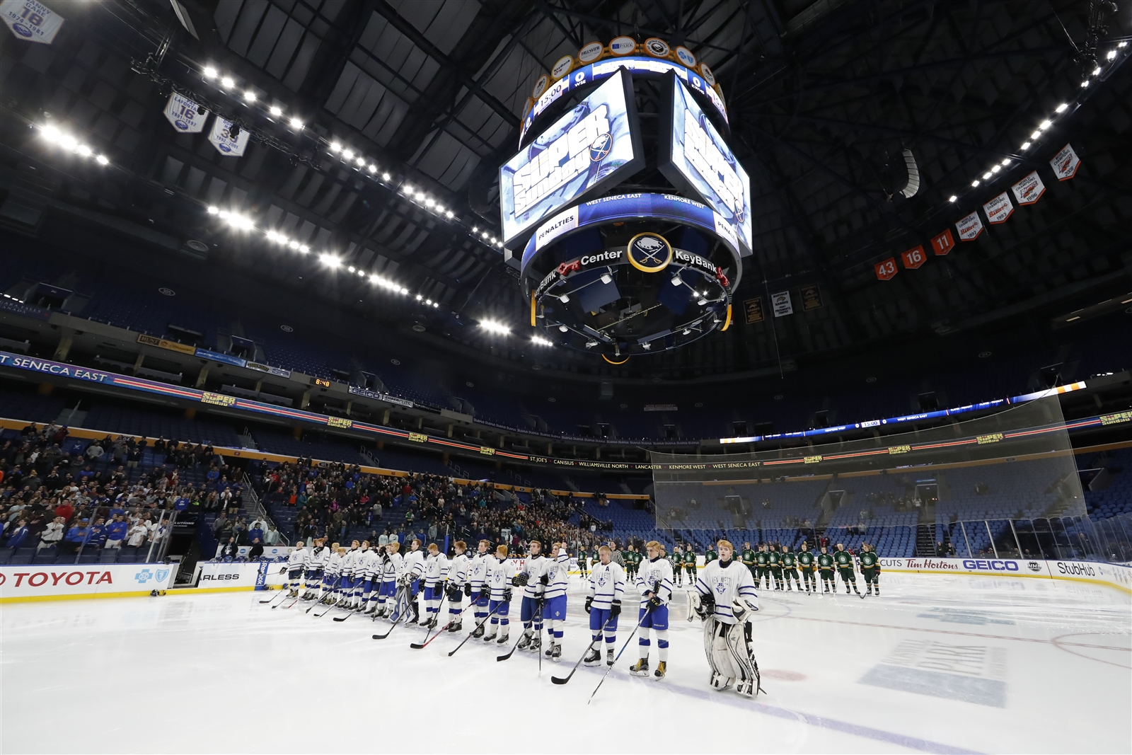 West Seneca East and  Kenmore West stand for a moment of silence in memory of Andrea McFall, wife of Hamburg hockey coach John McFall, at KeyBank Center Monday night prior to the  the Small School Section VI hockey championship game.