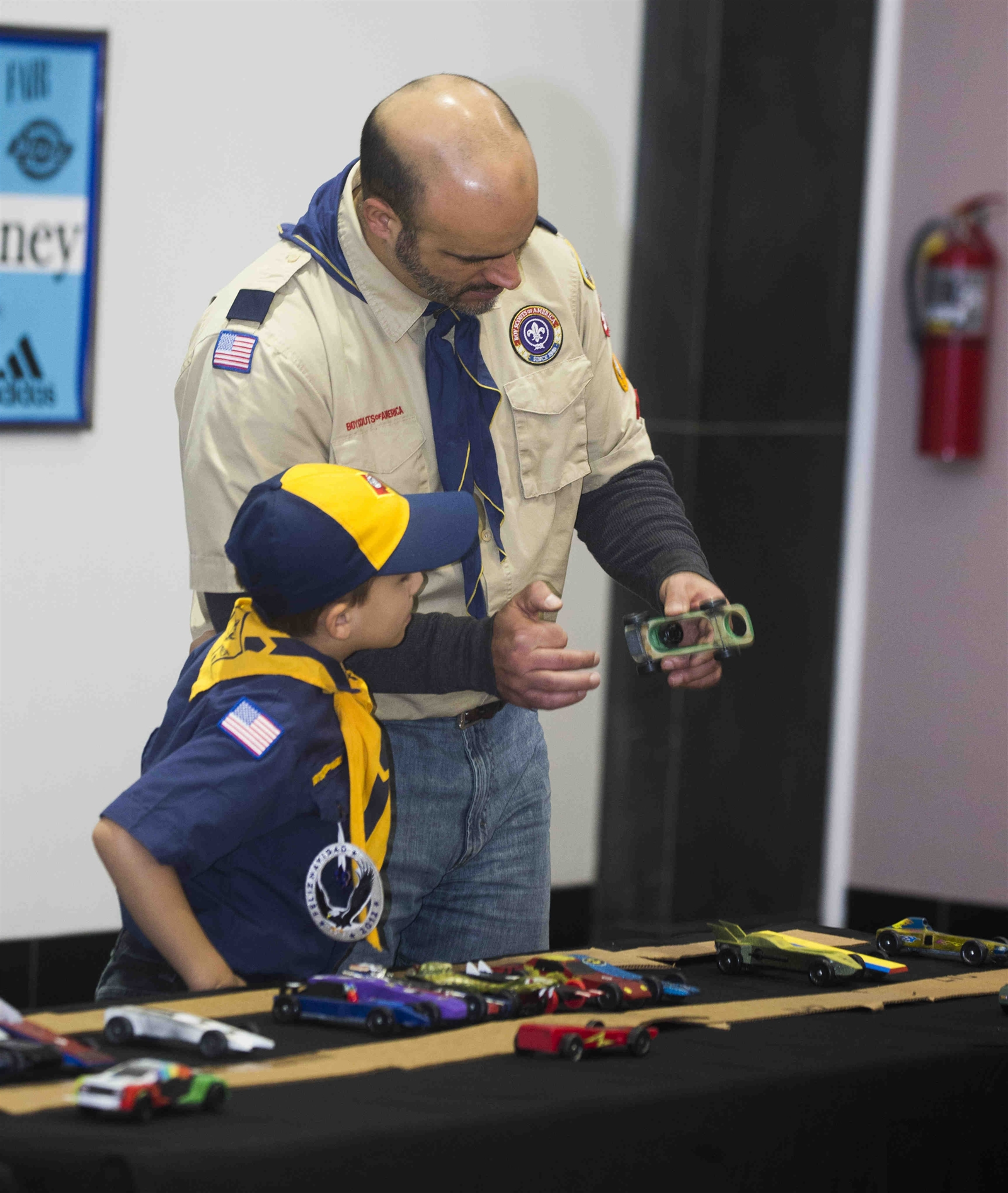 "Joe Ranalletta of Pack 563 and his son Bryce, 7, bottom, examine Bryce's pinewood derby car ""Batman"" at the Onondaga Cub Scout Packs Pinewood Derby races, held March 4 at the Eastern Hills Mall in Clarence."