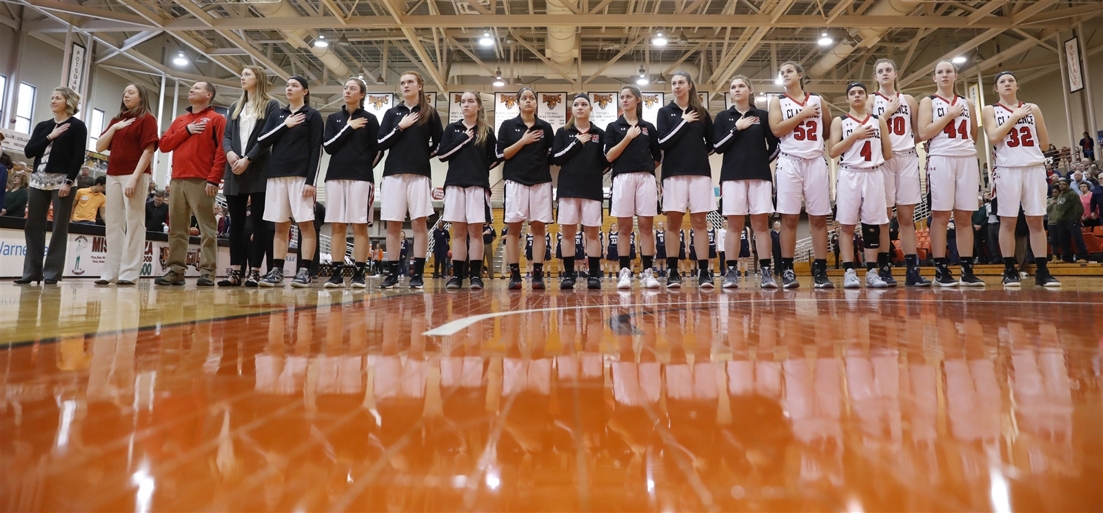 Clarence players and coaches stand for the national anthem prior to playing Our Lady of Mercy Monarchs for the New York State AA Far West Regional Championship at the Buffalo State Sports Arena on Saturday, March 11, 2017.