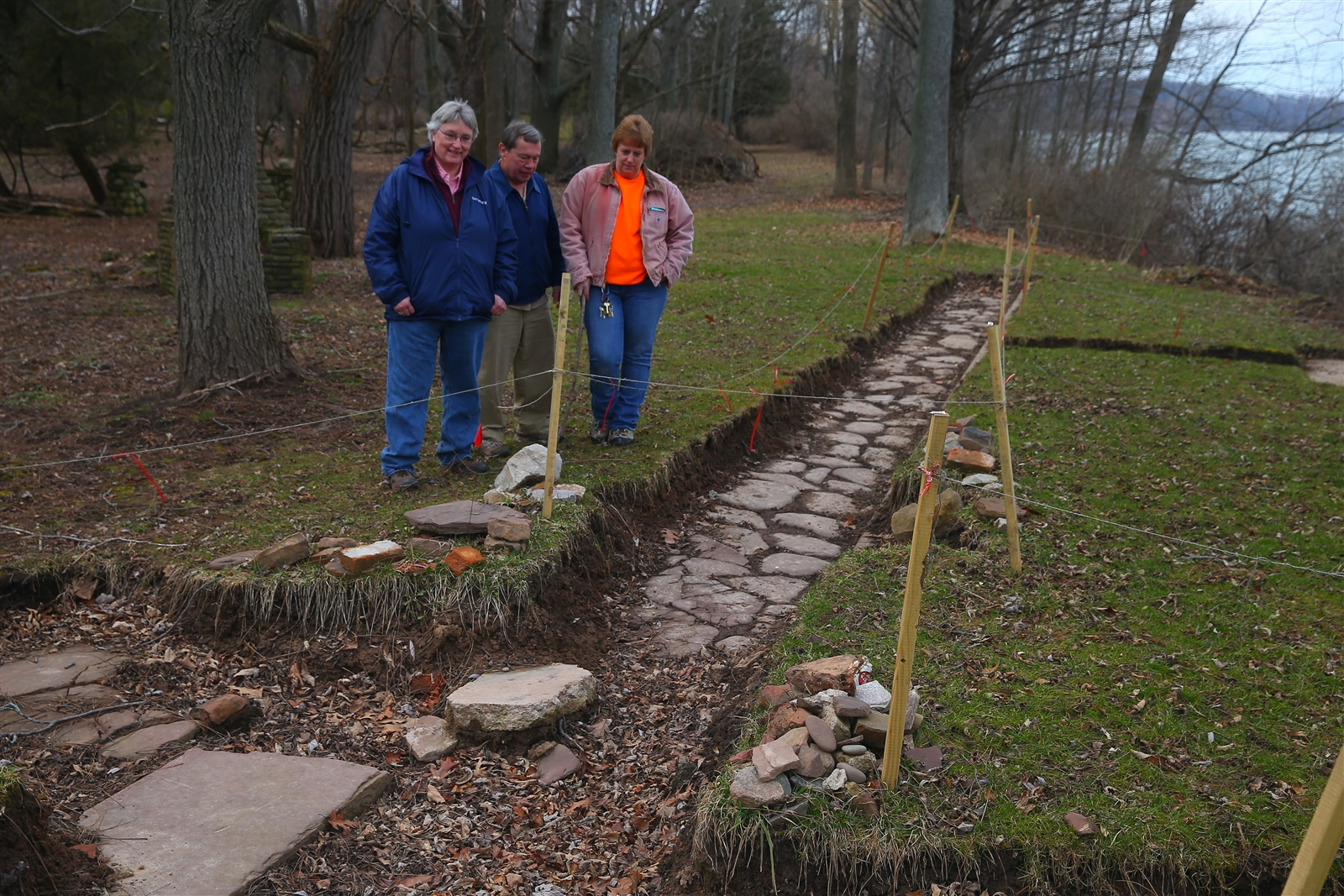 Golden Hill State Park volunteers Mike and Cheryl Wertman, left, stand with Park Manager Renee Campbell at the spot where the Wertmans excavated about a foot of soil to find the original stone path that ran along the lake. The path may have led to the original Drake House, which is gone. Much of the property has already eroded into Lake Ontario, and the losses continue every year.
