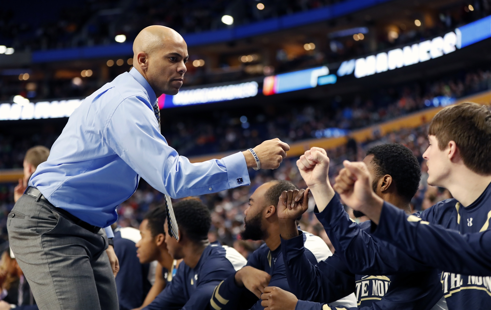 Mount St. Mary's coach Jamion Christian fist bumps his players after their first basket against Villanova.