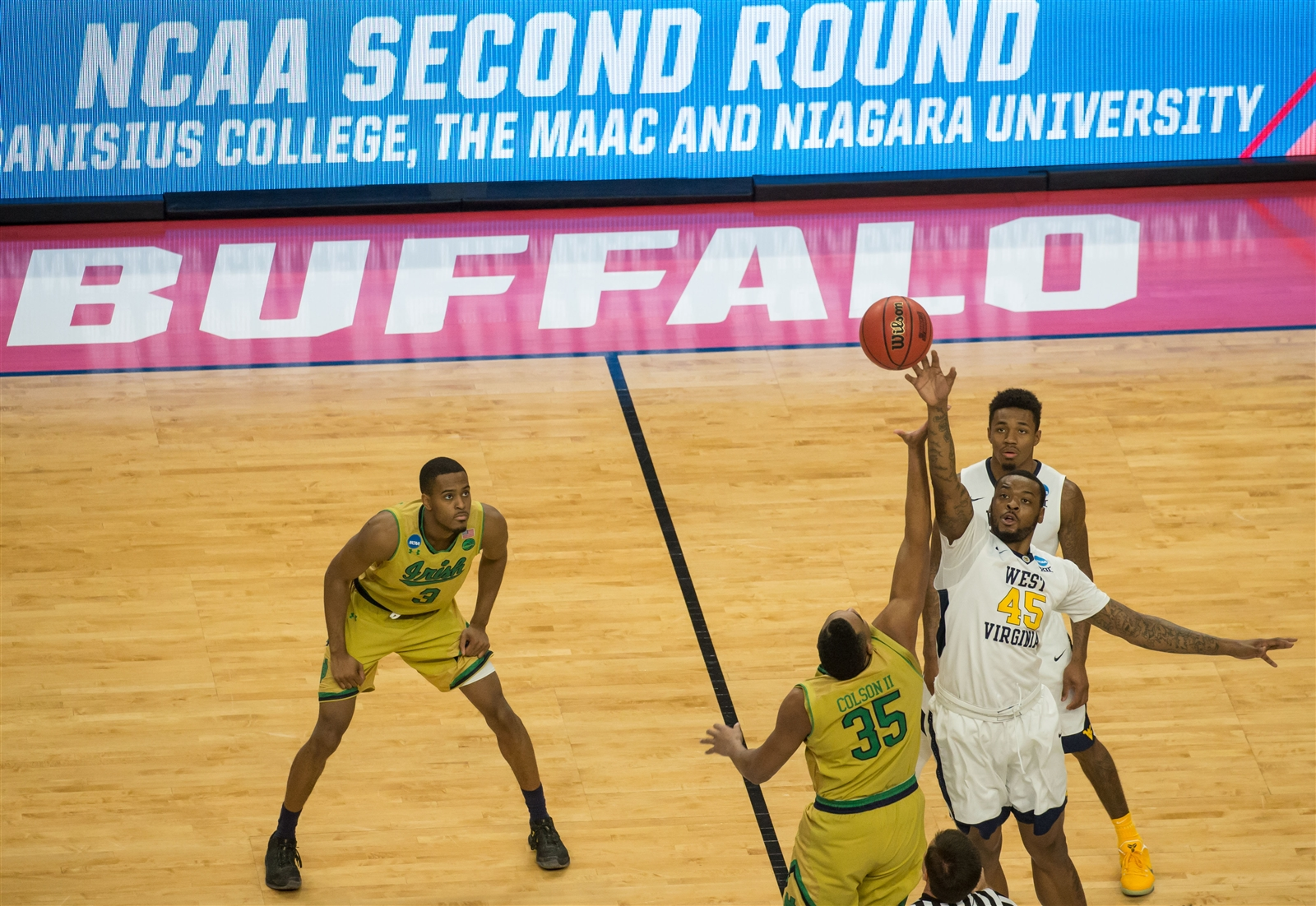 West Virginia's Elijah Macon (45) and Notre Dame's Bonzie Colson (35) take the tip off to start their NCAA Championship Tournament second round game at KeyBank Center, Saturday, March 18, 2017.
