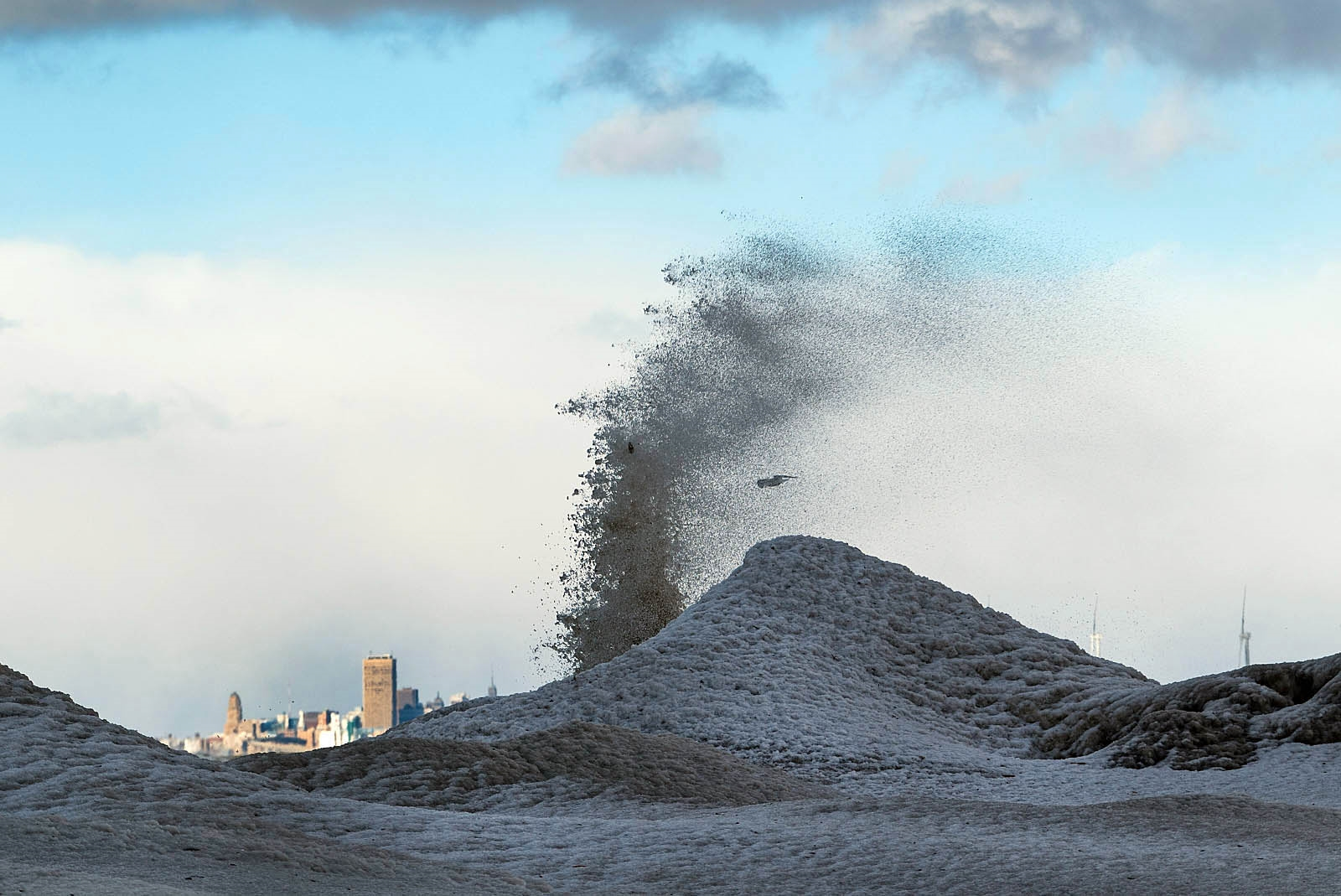 A mature ice volcano can grow as large as a house with a vent a yard or more wide. The Buffalo skyline can be seen in the background of this ice volcano at Hamburg Beach.