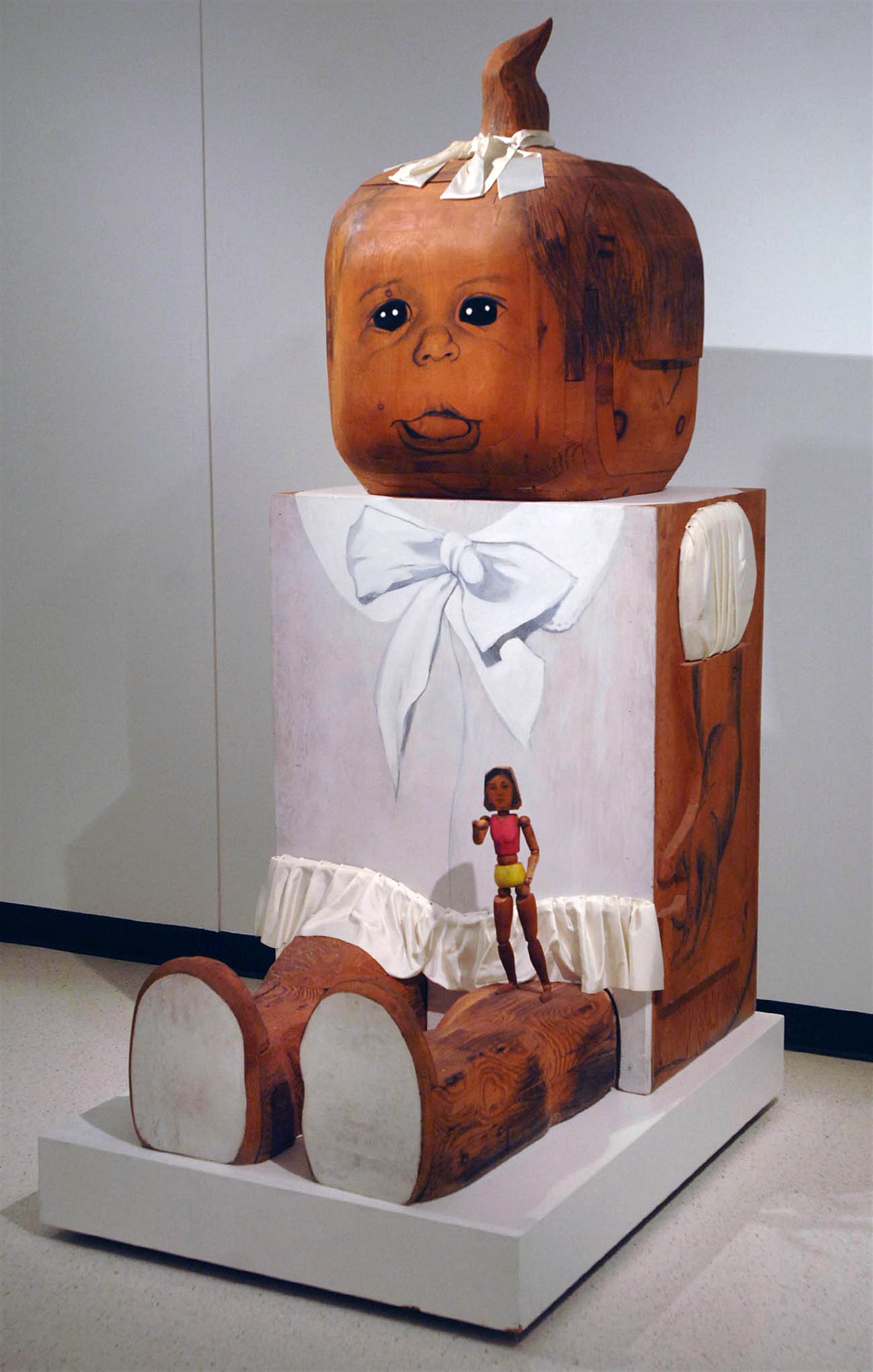"Baby Girl / Marisol / 1963.  Upon its purchase in 1964, Marisol's wood sculpture ""Baby Girl"" became an instant hit, charming children and disconcerting adults in equal measure. Its oddly bulbous head is juxtaposed against a square body, and a doll perched on the girl's left leg prompts viewers to ponder the expectations society places on an innocent infant expected to grow into a feminized adult."