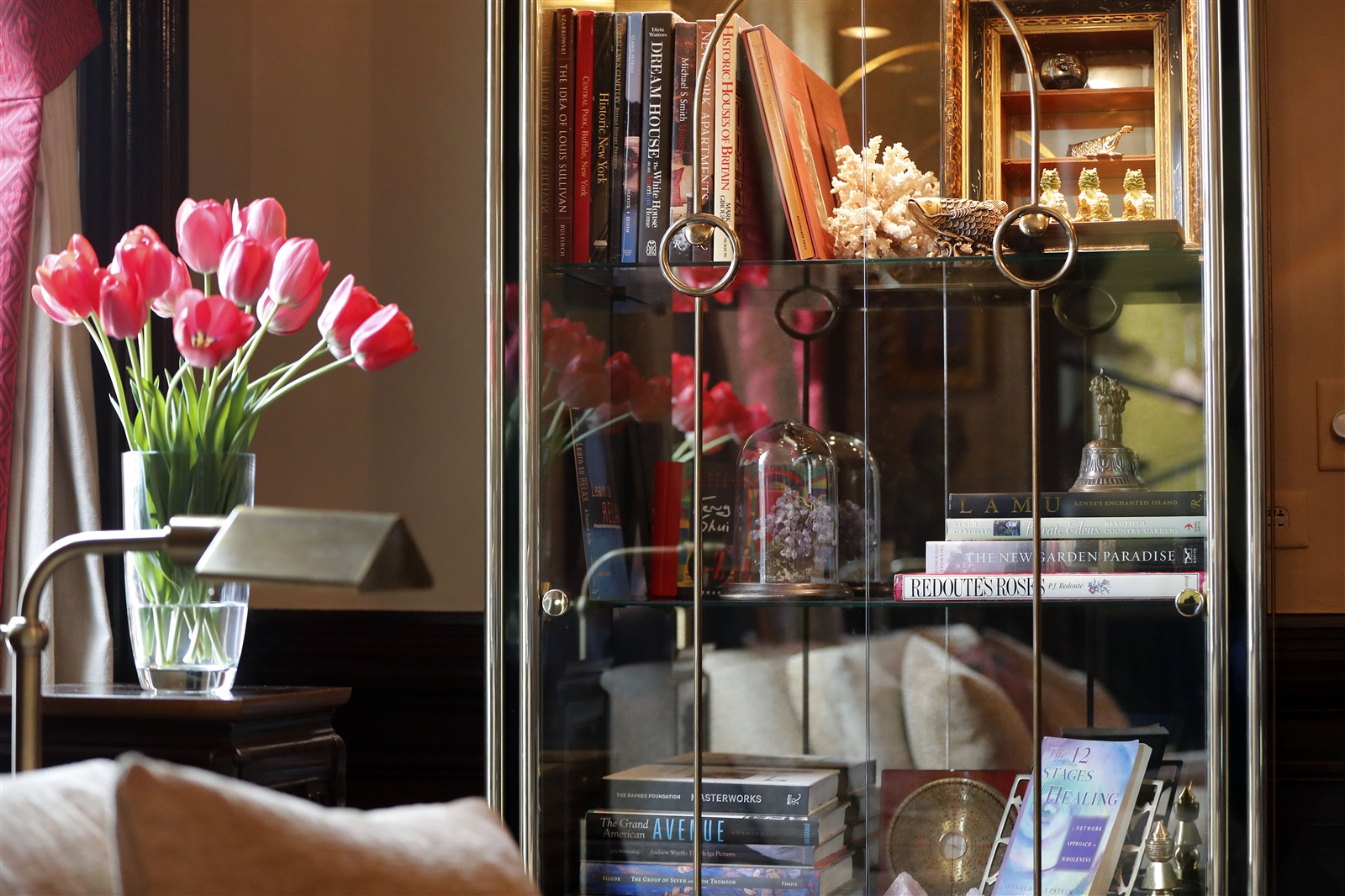An illuminated bookcase and fresh tulips are found in the Feng Shui Library on the first floor. (Designed by Mark Taylor Interiors and Feng Shui Your World.)