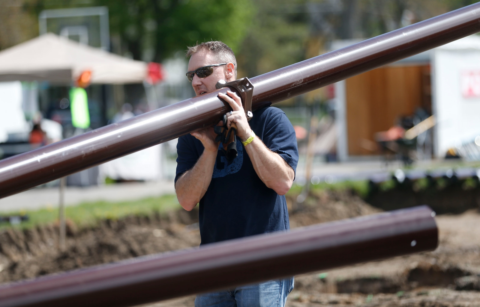 Volunteer Mike Ferguson carries a 16-foot post that will be used for a platform.