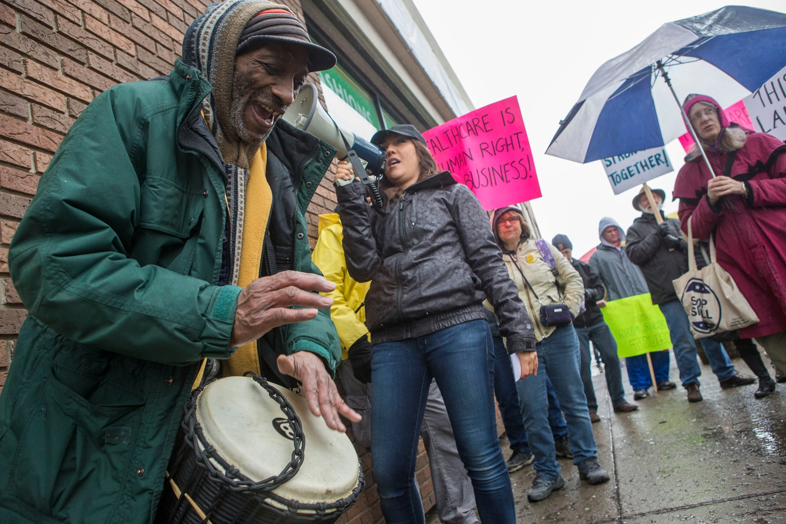 Ismail Johnson keeps the beat on his djembe as Theresa Joy uses the megaphone to lead chants during a stop outside the West Side Bazaar as protesters participate in the Immigrants Solidarity March on Grant Street.