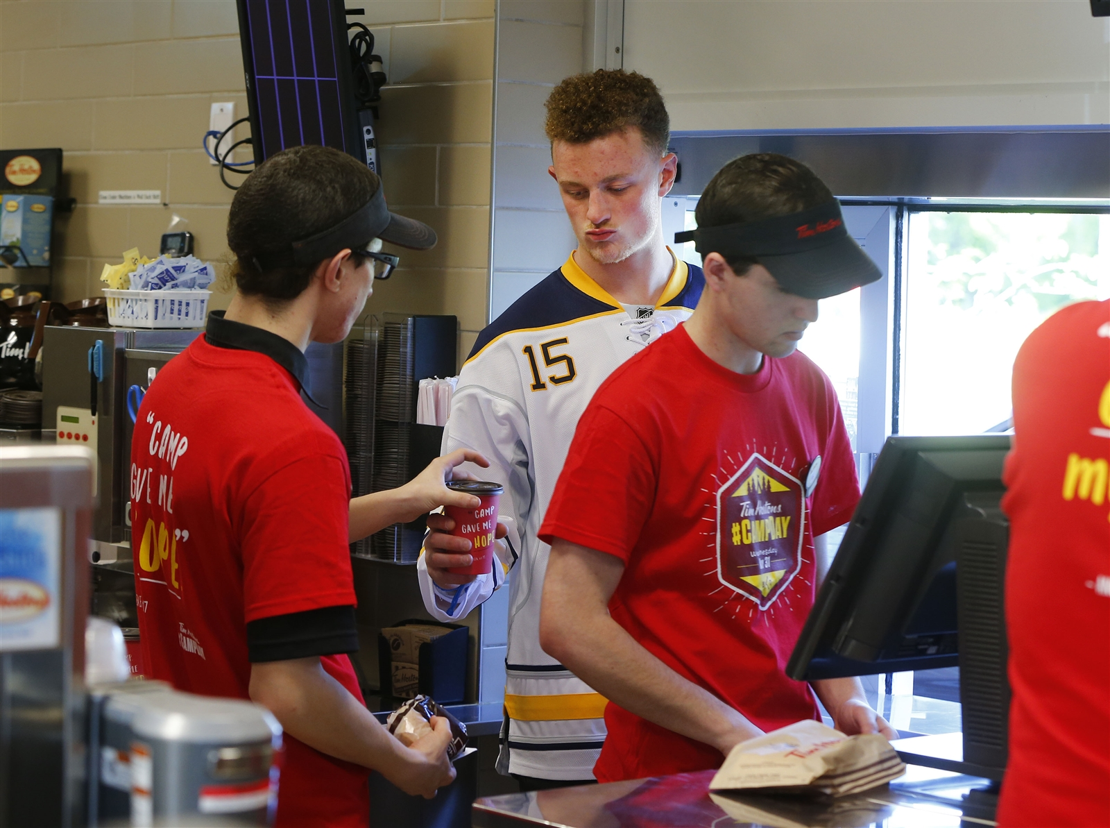 Jack Eichel hands out coffee to customers at the drive-thru window.