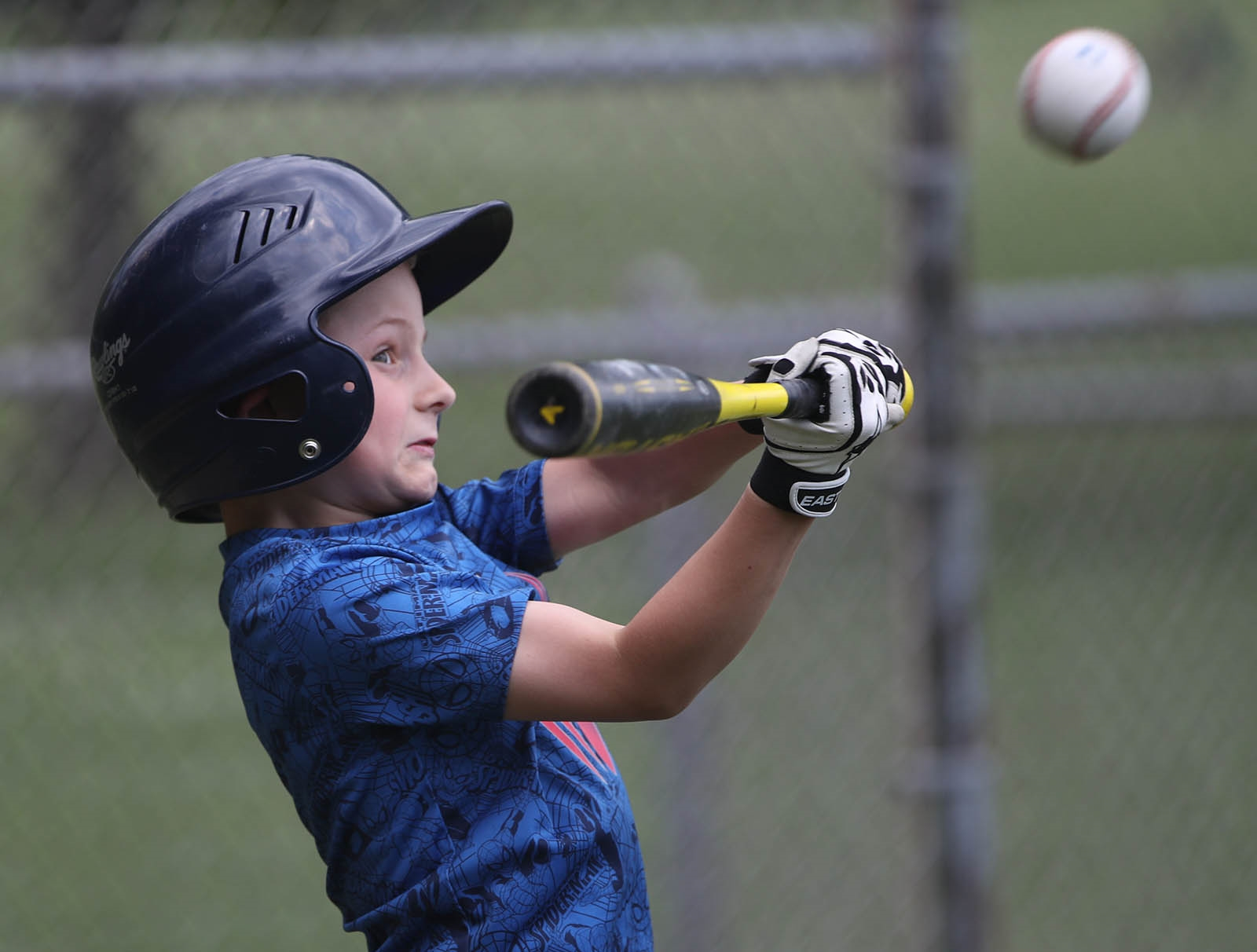 Little leaguer Cole McCleary, 7, connects with a pitch thrown by his grandfather Shaun McCleary while getting some batting practice.
