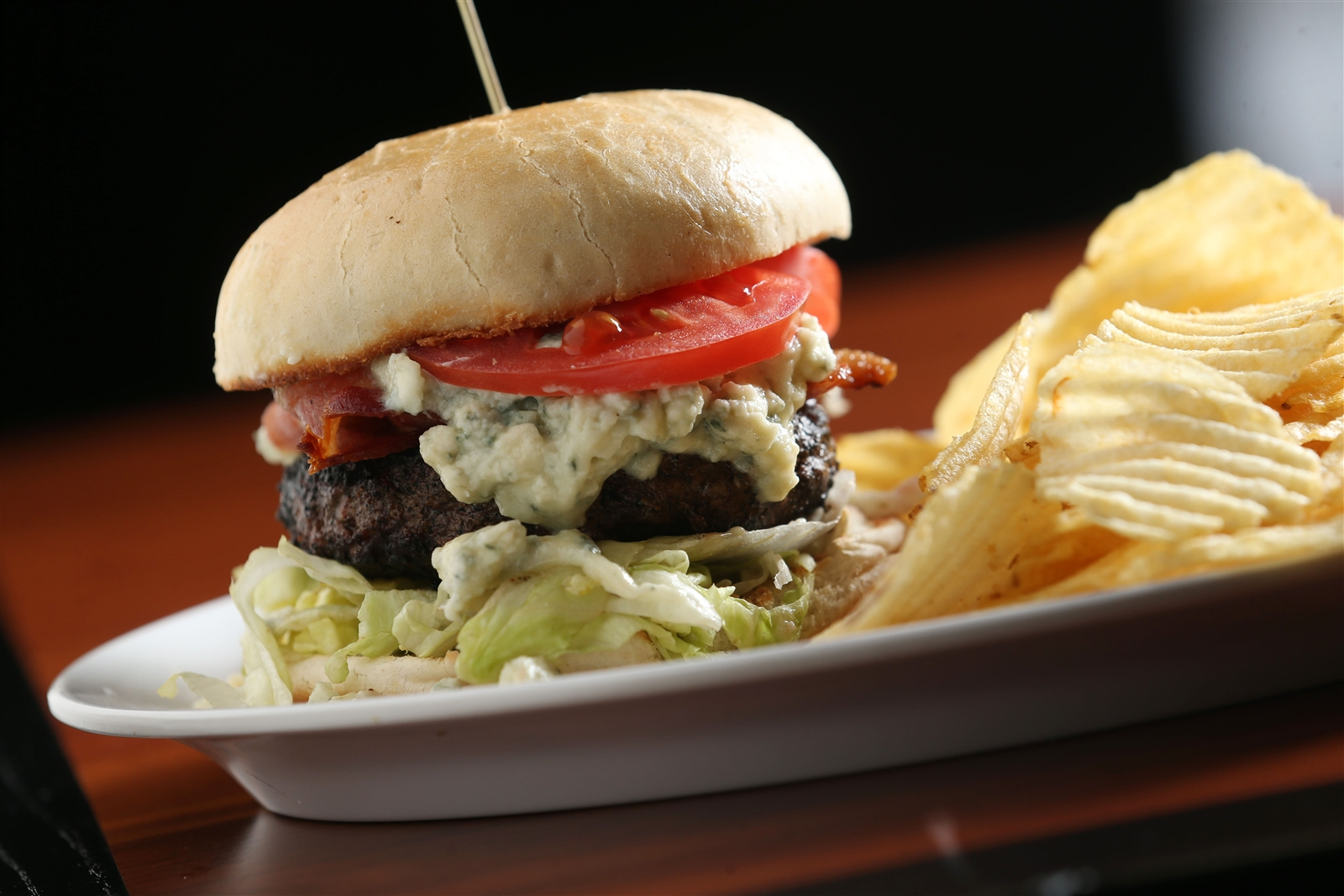 Rock Bottom Kitchen & Bar gives standard burgers an extra kick with The Raging Cajun Burger. The half pound burger is blackened cajun style and grilled, then topped with bacon, creamy bleu, lettuce and tomato. Rock Bottom is at 6261 Transit Rd.