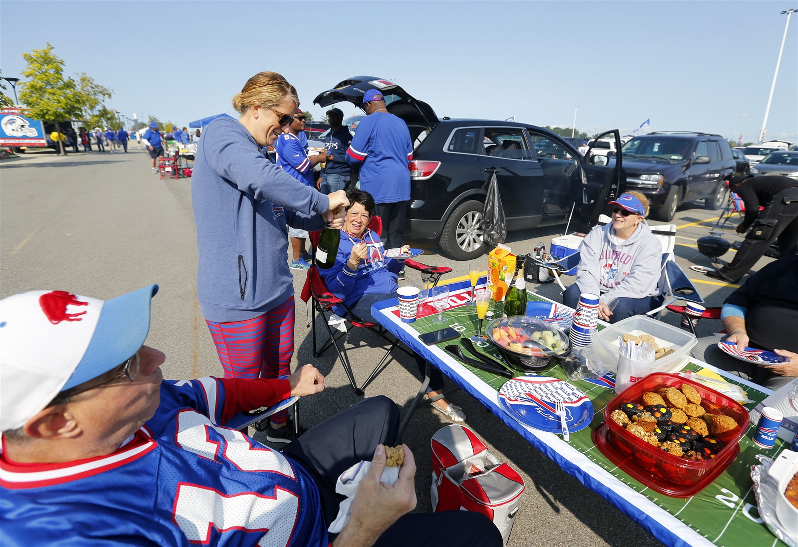 Kristin Cavaretta opens up a bottle of champagne in the parking lot before the game.