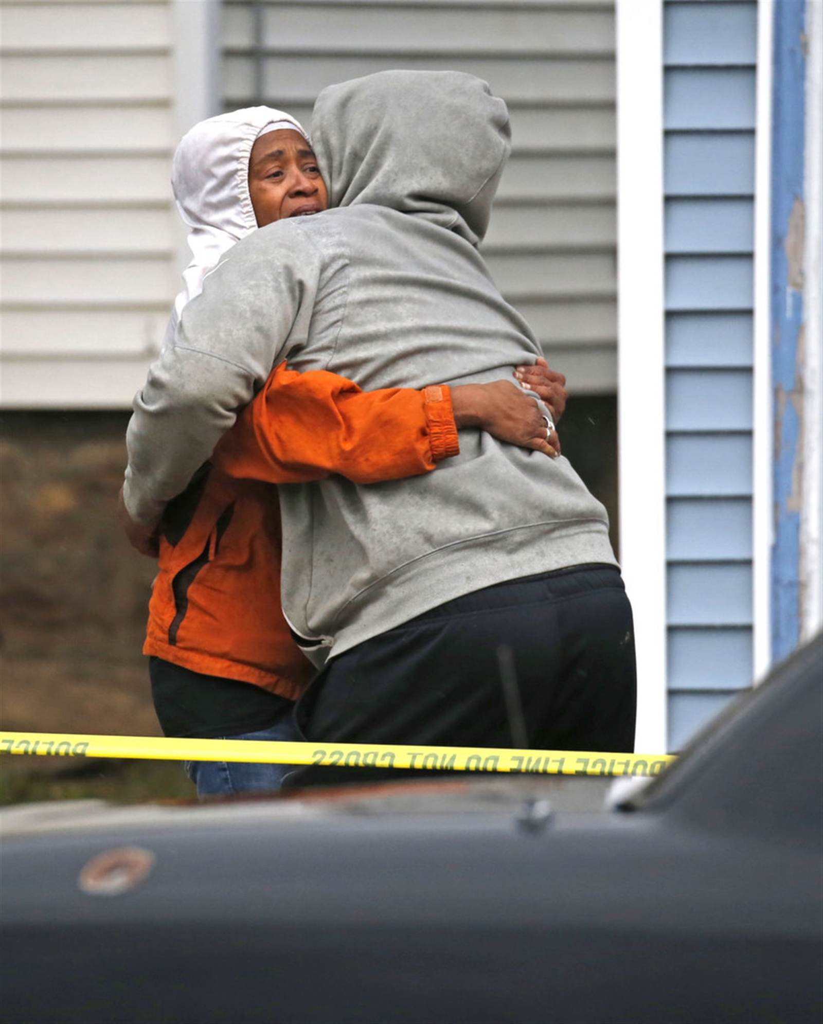Friends and family members console each other after learning the identification of a deceased shooting victim lying covered on the ground behind the Happy Time Way corner store on   Kensington Avenue in Buffalo.