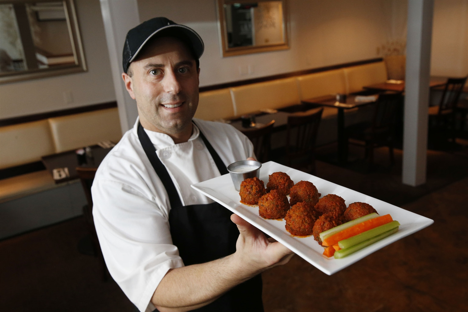 Owner and chef Paul Tsouflidis presents the Buffalo falafel fritters.
