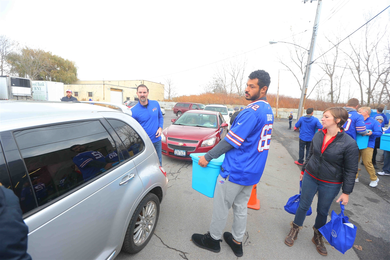 Buffalo Bills TE Logan Thomas carries a bin to a car.