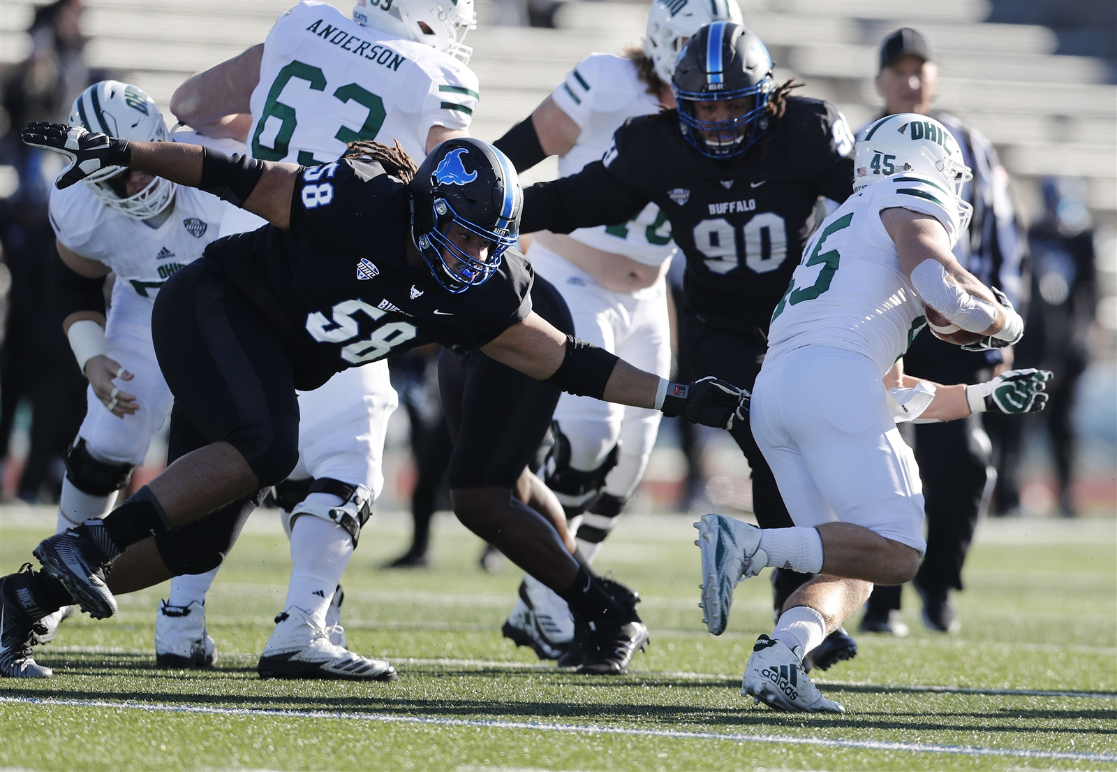 UB (58) Chris Ford tries to slow Ohio (45) A.J. Ouellette in the first half.