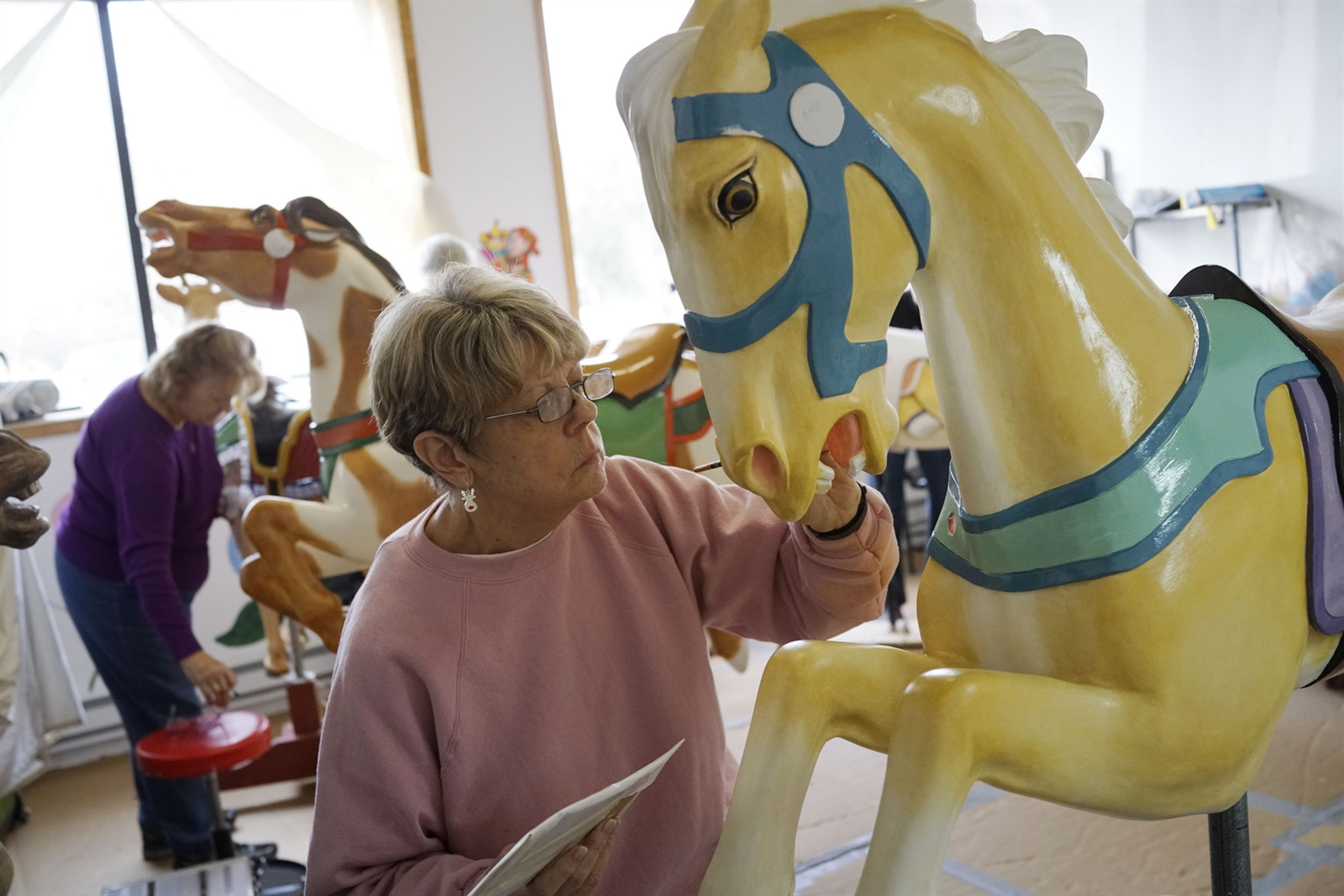 "Linda Chaffee paints the horse ""Scotty"" in a workshop across the street from the Herschell Carousel Museum in North Tonawanda. The carousel animals each will get two coats of wood sealer, two coats of oil-based primer, one coat of oil-based Dover white, two color coats of either artist's oil-based paint or sign painter's enamel, and five coats of clear varnish."