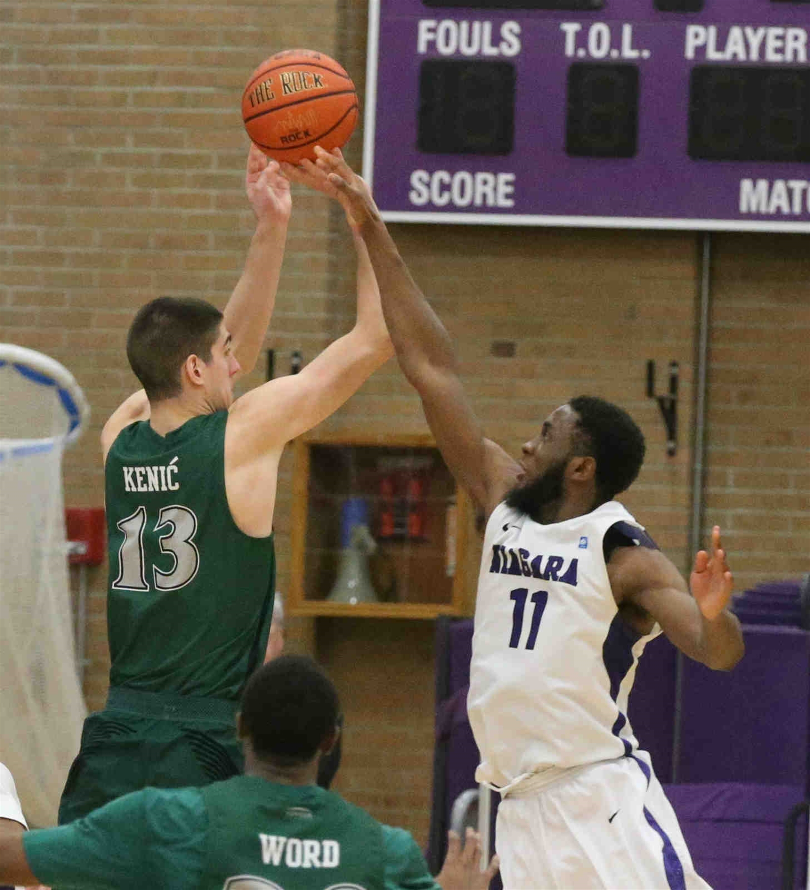 Niagara Purple Eagles forward Marvin Prochet (11) blocks the final shot of the game by Cleveland State Vikings forward Stefan Kenic (13) for the win.