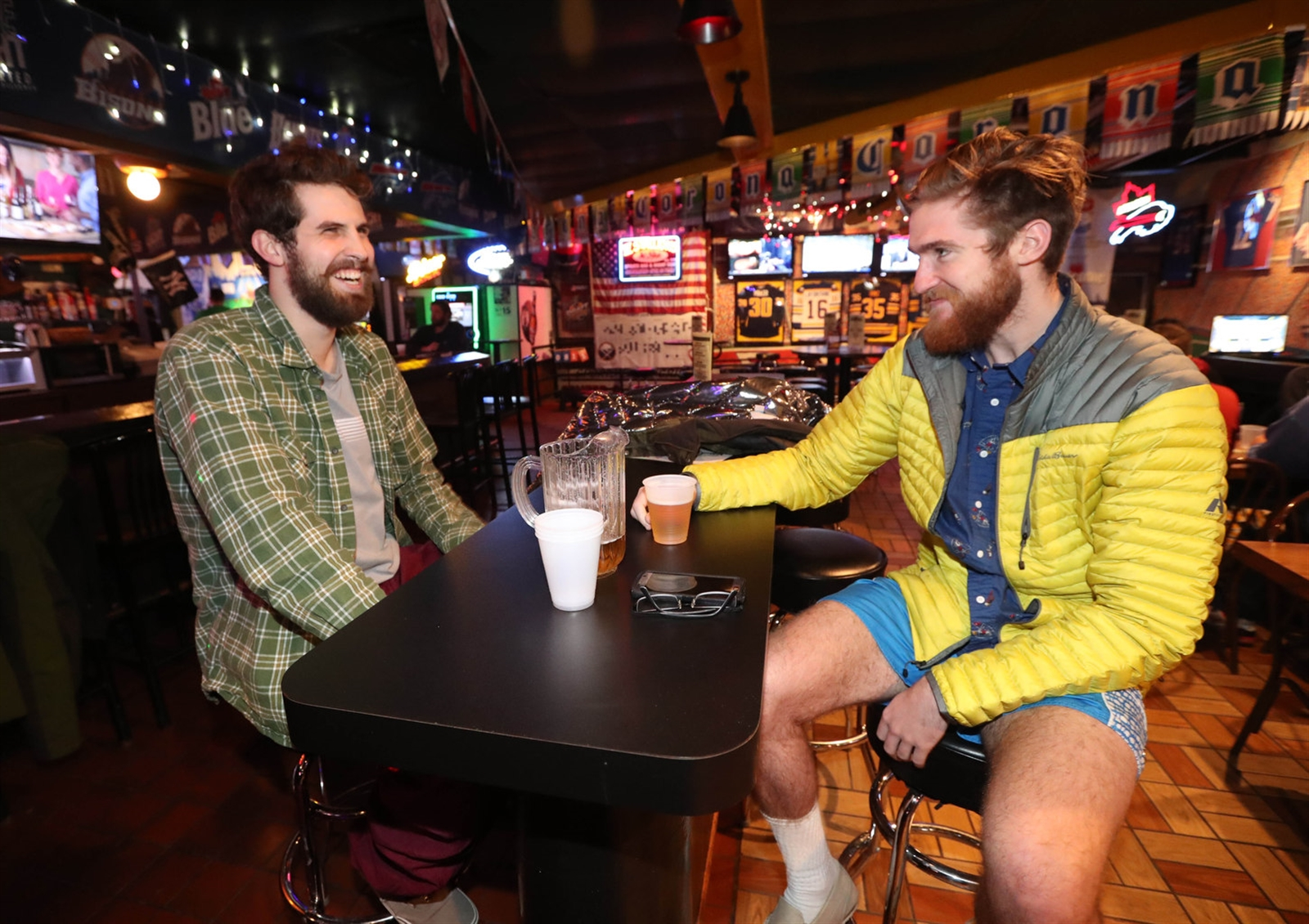 Justin Waldorf, of Eden, and Nicholas McDonagh, of Angola, have a beer after playing volleyball, Thursday, Dec. 21, 2017.