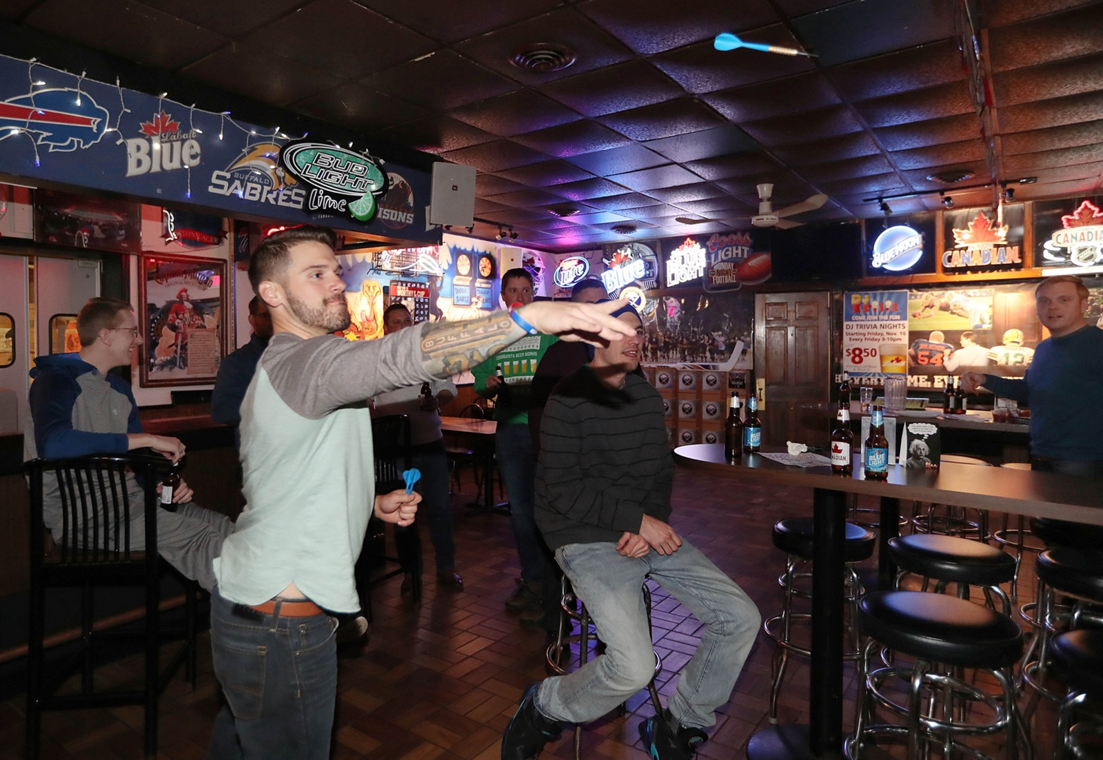 Corey Santonocito, of Depew, shoots darts, as he hangs out with former schoolmates of West Seneca West High School on their annual holiday outing, Thursday, Dec. 21, 2017.