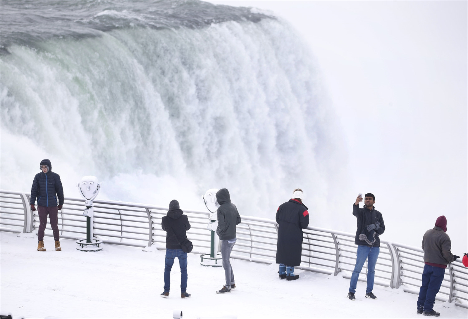 Tourists admire the American Falls at Prospect Point.